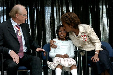 Her Excellency the Right Honourable Michaëlle Jean, Governor General of Canada, takes a quiet moment with her daughter Marie‑Éden and her husband, His Excellency Jean‑Daniel Lafond, during a public ceremony at Edmonton City Hall on May 5, 2006.  The ceremony showcased Edmonton's rich cultural diversity, including Aboriginal hoop dancers, a youth choir, the Cariwest Performers, a brass ensemble, a Franco-Albertan group and a reading by the Poet Laureate. The Governor General also presented a Meritorious Service Medal to Olympian Becky Scott and the Caring Canadian Award to four Albertans. The Governor General conducted her first regional visit to Alberta from May 4 to 6, 2006. During her three-day visit, Her Excellency focused on building dialogue and forging links with as many Albertans as possible, including the military and their spouses, school children and youth, as well as community volunteers. This was her 7th provincial visit since the beginning of her mandate.