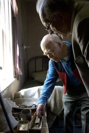 His Excellency Jean-Daniel Lafond and Steve Rowan from the Fort Simpson Historical Society look at old objects found in Albert Faille's House in Fort Simpson, N.W.T. on June 21, 2006.  Albert Faille was a famous explorer of gold who lived on the shore of the Nahanni River until he died in 1973.  His house is now a museum.  Their Excellencies celebrated National Aboriginal Day in Fort Simpson.  During their time in the community, they took part in a fire ceremony, a tour of the town, a meeting with local leaders, elders and first nations groups, as well as a community feast.