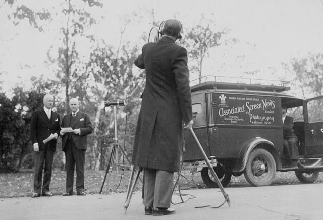 The Earl of Bessborough (left) and Prime Minister R.B. Bennett are filmed by Roy Tash.      Date: 1930s. Photographer: Roy Tash. Reference: Library and Archives Canada, PA-067244.