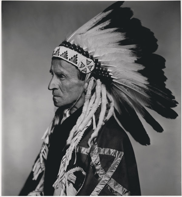 Lord Tweedsmuir was made honorary chief of the Blood Indians (now called the Kainah Nation) during his visit to Alberta (September 1936).  Date: 1937. Photographer: Yousuf Karsh. Reference: Library and Archives Canada, e010751819.