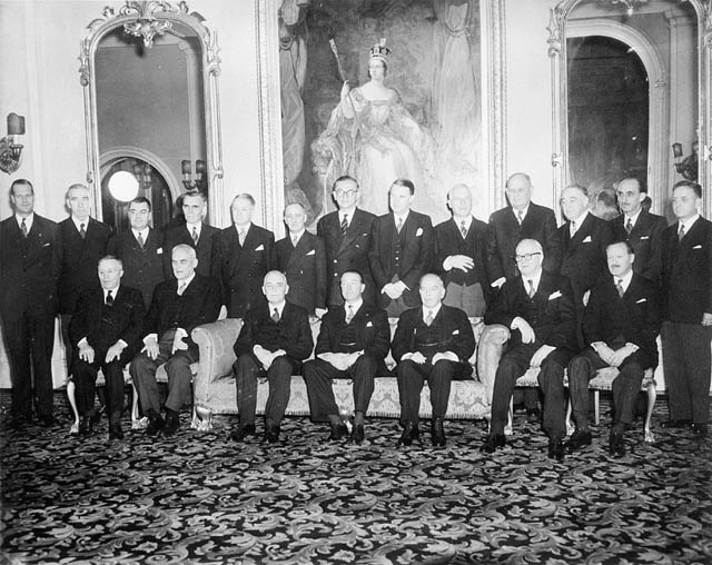 Viscount Alexander (seated, at centre) with former Prime Minister Mackenzie King and newly elected Prime Minister Louis St.-Laurent in a group photo of the Cabinet after the swearing-in ceremony at Rideau Hall. Date: November 15, 1948. Photographer: Unknown.   Reference: Library and Archives Canada, C-031308.