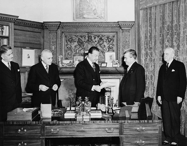 Viscount Alexander of Tunis (at centre), Governor General of Canada (1946-1952), receives the bill concerning the Terms of the Union of Newfoundland with Canada.  Date: 1949. Photographer: National Film Board of Canada. Reference: Library and Archives Canada, C-021401.