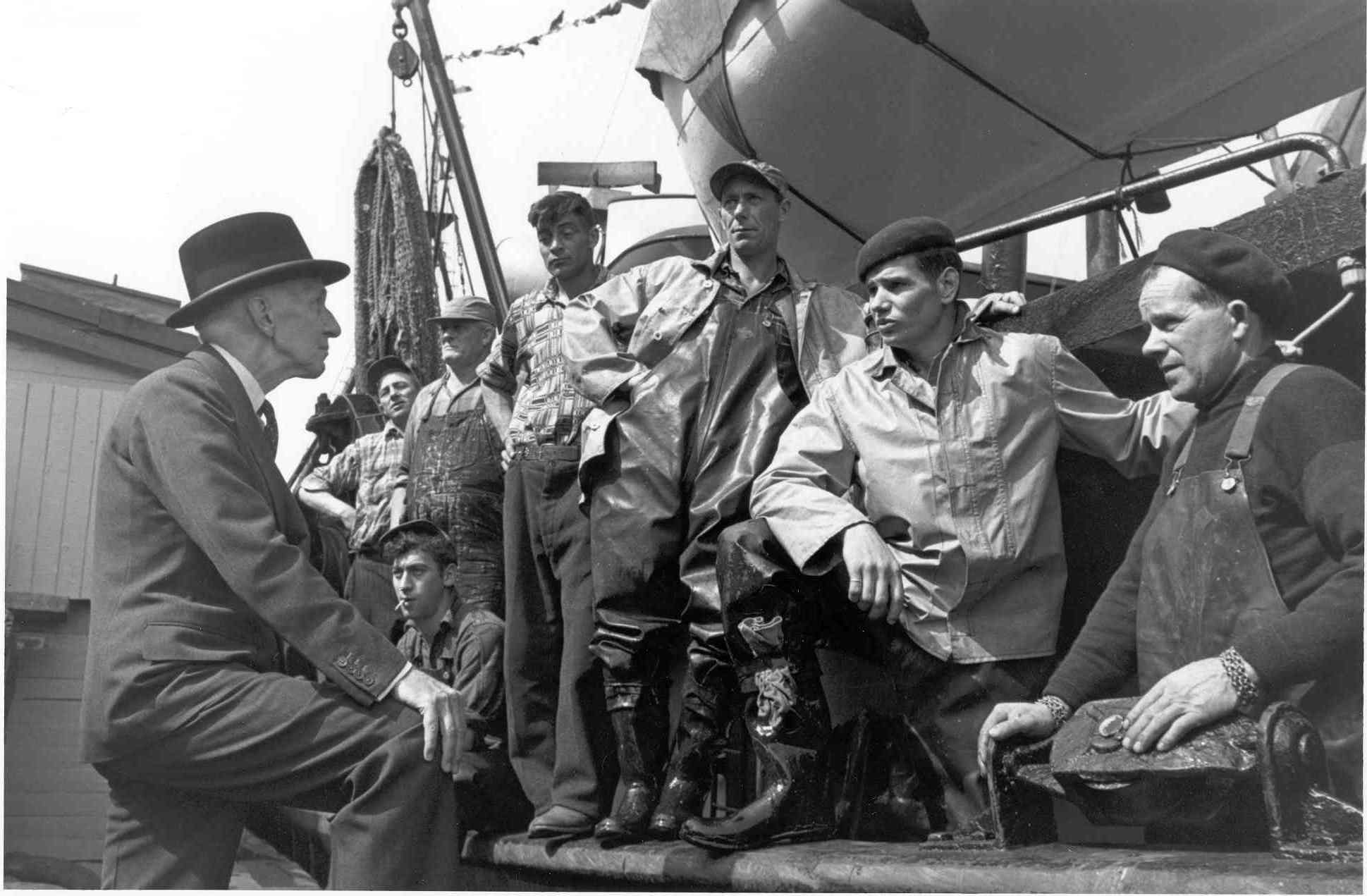 Governor General Vincent Massey speaks with a group of fishermen (St. John's, Newfoundland). Date: August 1955. Photographer: Gar Lunney, National Film Board of Canada. Reference: National Archives of Canada, PA-211709.