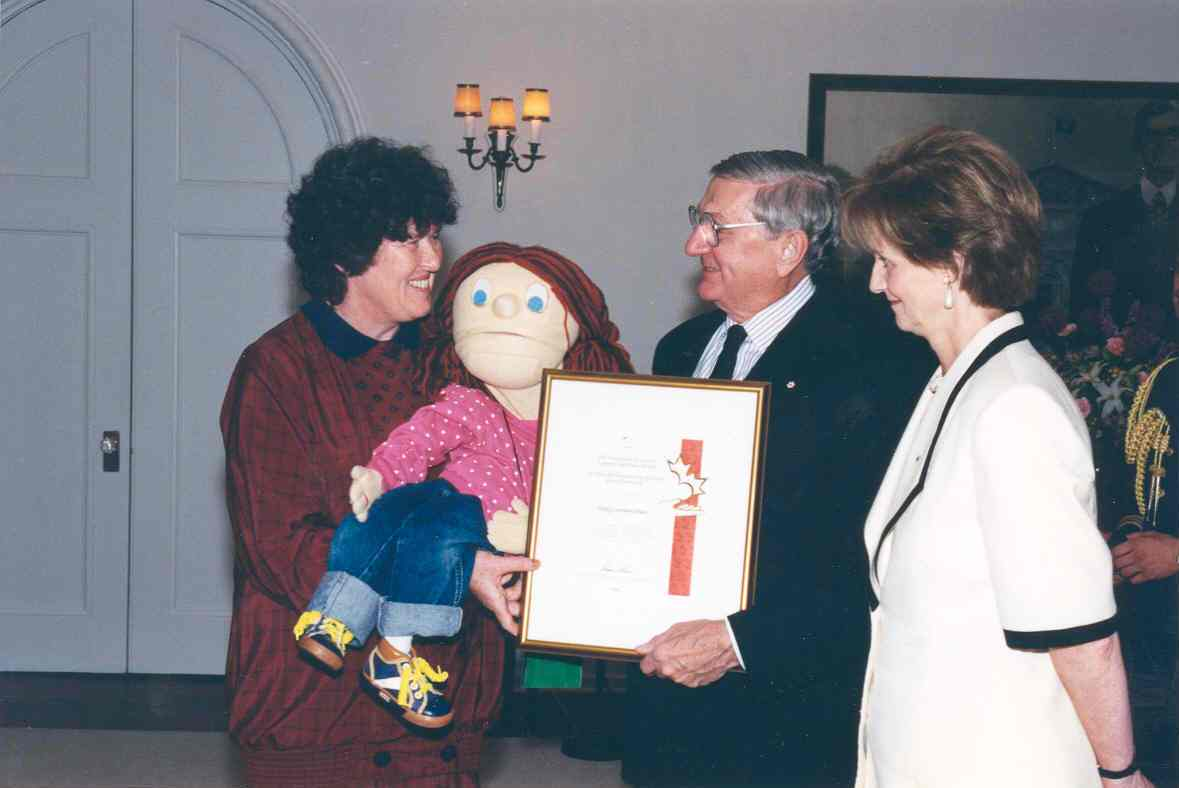 Governor General Roméo LeBlanc presents the Governor General's Caring Canadian Award to Mrs. Sally L. Olsen, for her contributions to the development of children. Date: December 12, 1996. Photographer: Sgt Christian Coulombe, Rideau Hall. Reference: GGC97-563-19.
