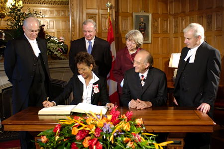 In the Senate's Chamber, Their Excellencies the Right Honourable Michaëlle Jean and Mr. Jean-Daniel Lafond sign the Government of Canada Golden Book in the presence of The Honourable Dan Hays, Speaker of the Senate, the Prime Minister Martin, Mrs. Martin and The Honourable Peter Milliken, Speaker of the House of Commons. In addition, the Governor General signs the proclamation marking her accession.