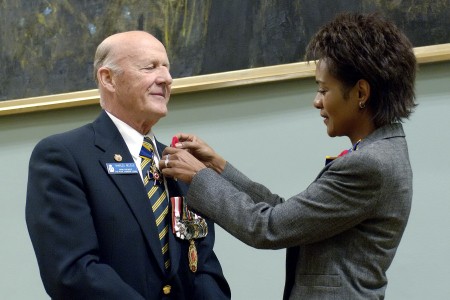 Her Excellency the Right Honourable Michaëlle Jean, Governor General and Commander-in-Chief of Canada and patron of the Royal Canadian Legion, pins a poppy on the lapel of the Grand President of the Legion, Charles H. Belzile, on Tuesday, October 25, 2005, at Rideau Hall.
