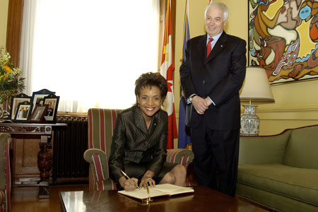 Her Excellency the Right Honourable Michaëlle Jean, Governor General of Canada, signs the Gold Book during her visit with the Honourable James K. Bartleman, Lieutenant Governor of Ontario, on February 21, 2006, in Toronto.