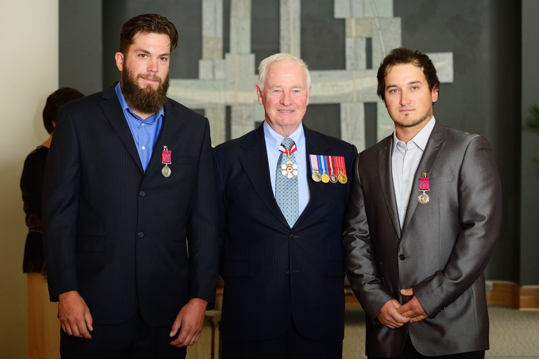 The Governor General presented the Medal of Bravery to Charles-Antoine Desautels, M.B. and Simon Lalonde, M.B. On October 24, 2013, Charles-Antoine Desautels and Simon Lalonde rescued a female co-worker who had fallen from a footbridge into the St. Lawrence River, in Sept-Îles, Quebec. The workers were leaving their construction site when the woman fell four metres into the freezing water. Her safety vest did not deploy and she began to sink under water. Without any thought for their own safety, Messrs. Desautels and Lalonde jumped from the footbridge, pulled the victim to the surface, and towed her back to the dock where others were able to help them get out of the water.