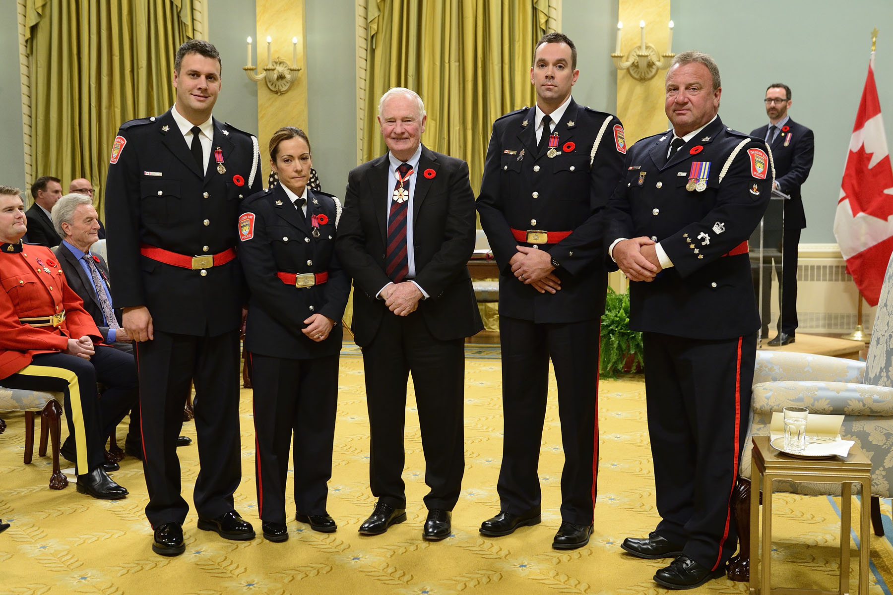 On October 22, 2011, constables James Elvish, M.B. and Bar, Ryan Krupa, M.B., Andrea MacInnis, M.B., and Kristofer Poling, M.B., rescued several people from a burning hotel in Thunder Bay, Ontario. After helping to evacuate occupants from another part of the building, these officers made their way to a three-storey tower attached to the hotel. Without any protective clothing or breathing apparatus, they made their way up to the third floor through the thick, black smoke. They checked every room and assisted the remaining occupants outside to safety. 
