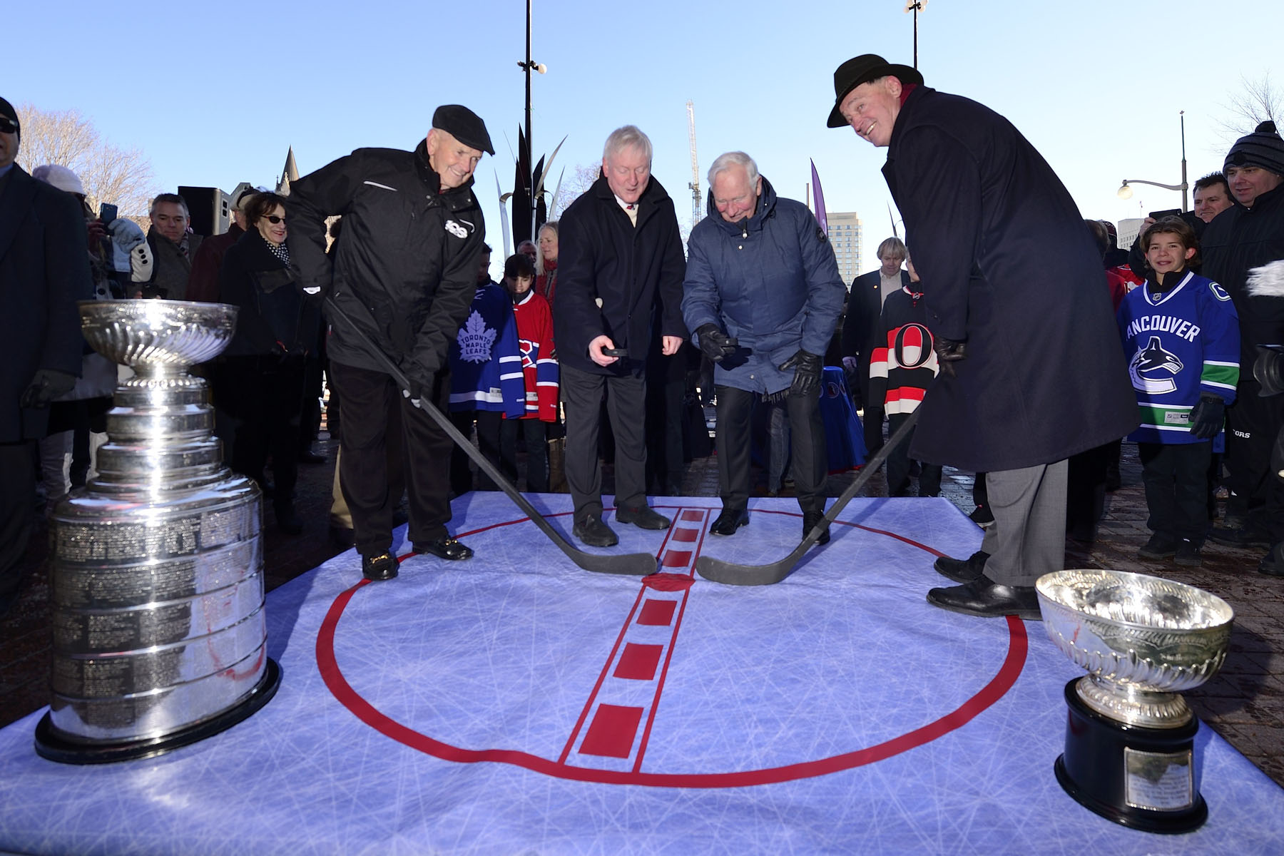 His Excellency, joined by Mr. Hunter and NHL alumni Frank Maholvich (right) and Dave Keon (left) participated in the groundbreaking of the Lord Stanley's Gift Monument with a ceremonial puck-drop.