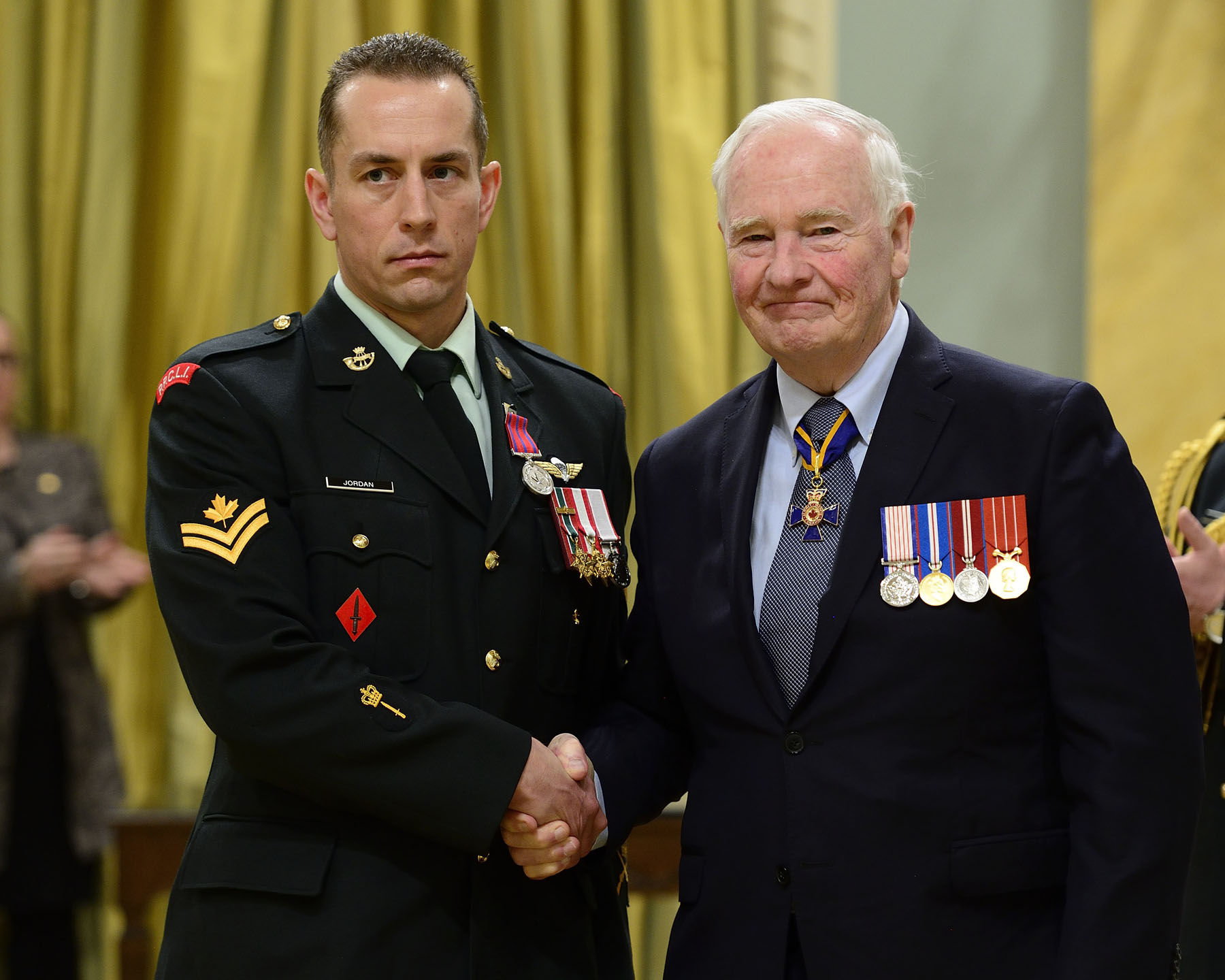 On October 2, 2014, Master Corporal Tyler Jordan, M.B., rescued a fellow parachutist who had become entangled in high-voltage power lines during a night jump near Smith Falls, Ontario. Despite the risk posed by the live wires, Master Corporal Jordan convinced firefighters to raise him in their crane and bucket to reach the victim's side. He then cut the victim free from the wires and pulled him into the safety of the insulated bucket.