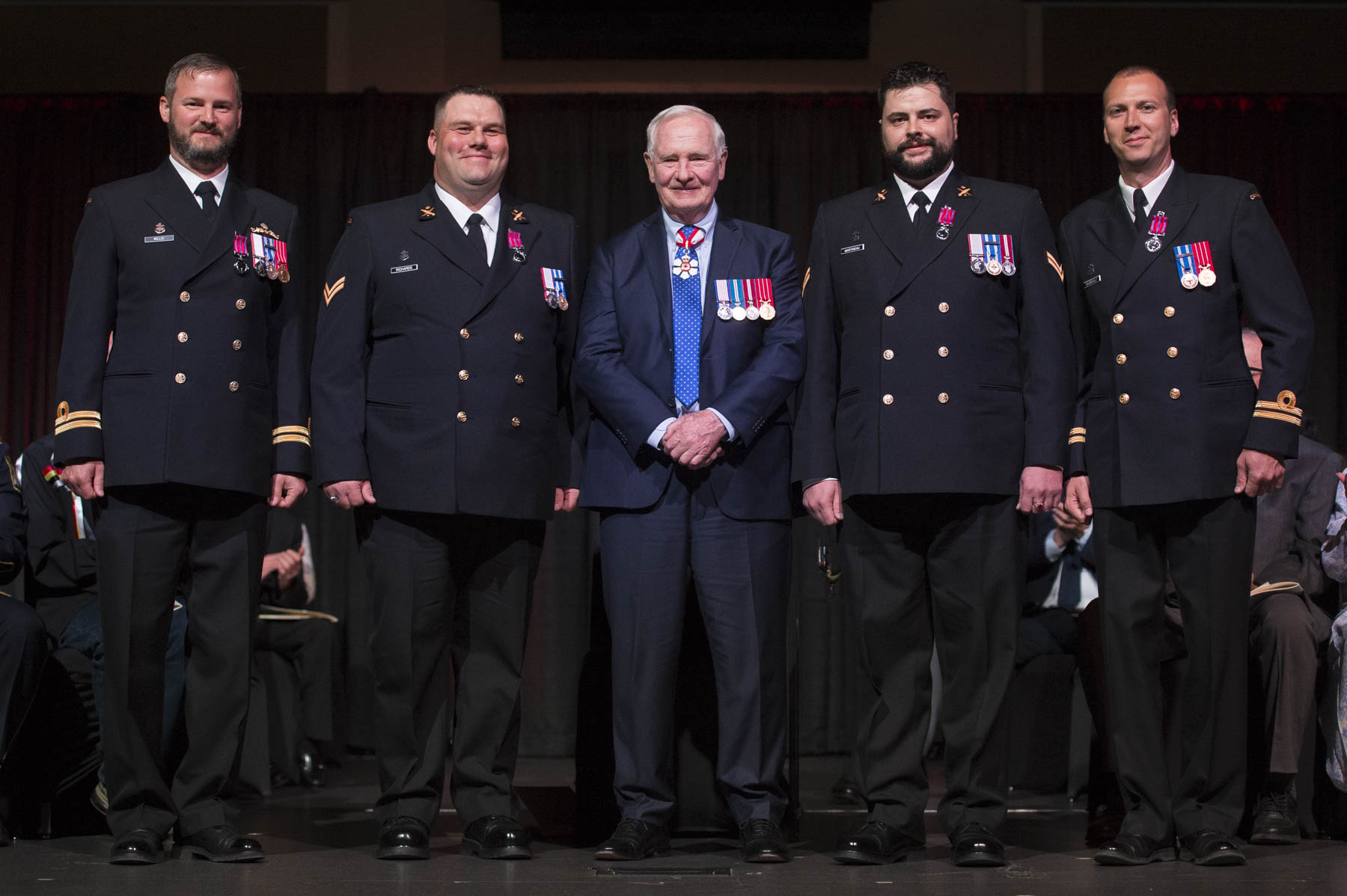 His Excellency presented the Medal of Bravery to Lieutenant(N) Samuel Gaudreault, M.B., C.D., Leading Seaman Jean-François Martineau, M.B., Able Seaman James Richards, M.B., and Lieutenant(N) Daniel Willis, M.B., C.D. On November 15, 2014, Lieutenant(N) Samuel Gaudreault, Leading Seaman Jean-François Martineau, Able Seaman James Richards and Lieutenant(N) Daniel Willis rescued several people from a burning building in Antalya, Turkey. When the top floor caught fire, lieutenants Gaudreault and Willis grabbed an extinguisher and ran upstairs to fight the fire and help people escape. Leading Seaman Martineau and Able Seaman Richards were walking by when they saw the blaze. They immediately entered the building and ran upstairs. Able Seaman Richards ran across the room to a balcony where a man was trying to catch a water hose being thrown from below. Lieutenant(N) Willis went back downstairs to retrieve wet towels to cover their faces. With Leading Seaman Martineau leading the way, the rescuers extinguished the fire and brought the last victim to safety.