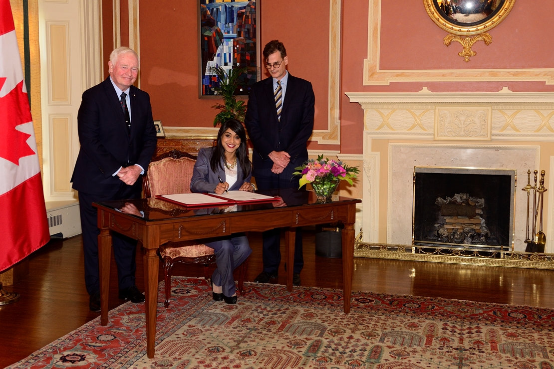 The minister, the Governor General and the Deputy Clerk of the Privy Council signed the oath book to formally attest to the swearing-in.