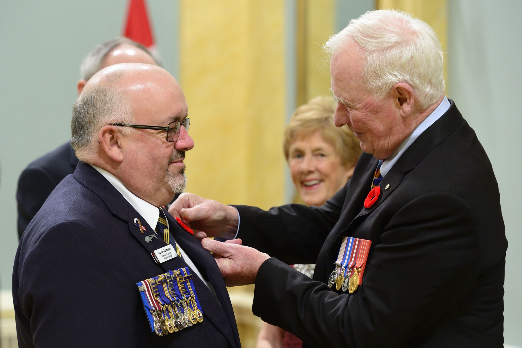 After receiving the first symbolic poppy of the campaign from Mr. David Flannigan, Dominion President of The Royal Canadian Legion, the Governor General presented a poppy to M. Flannigan in turn.