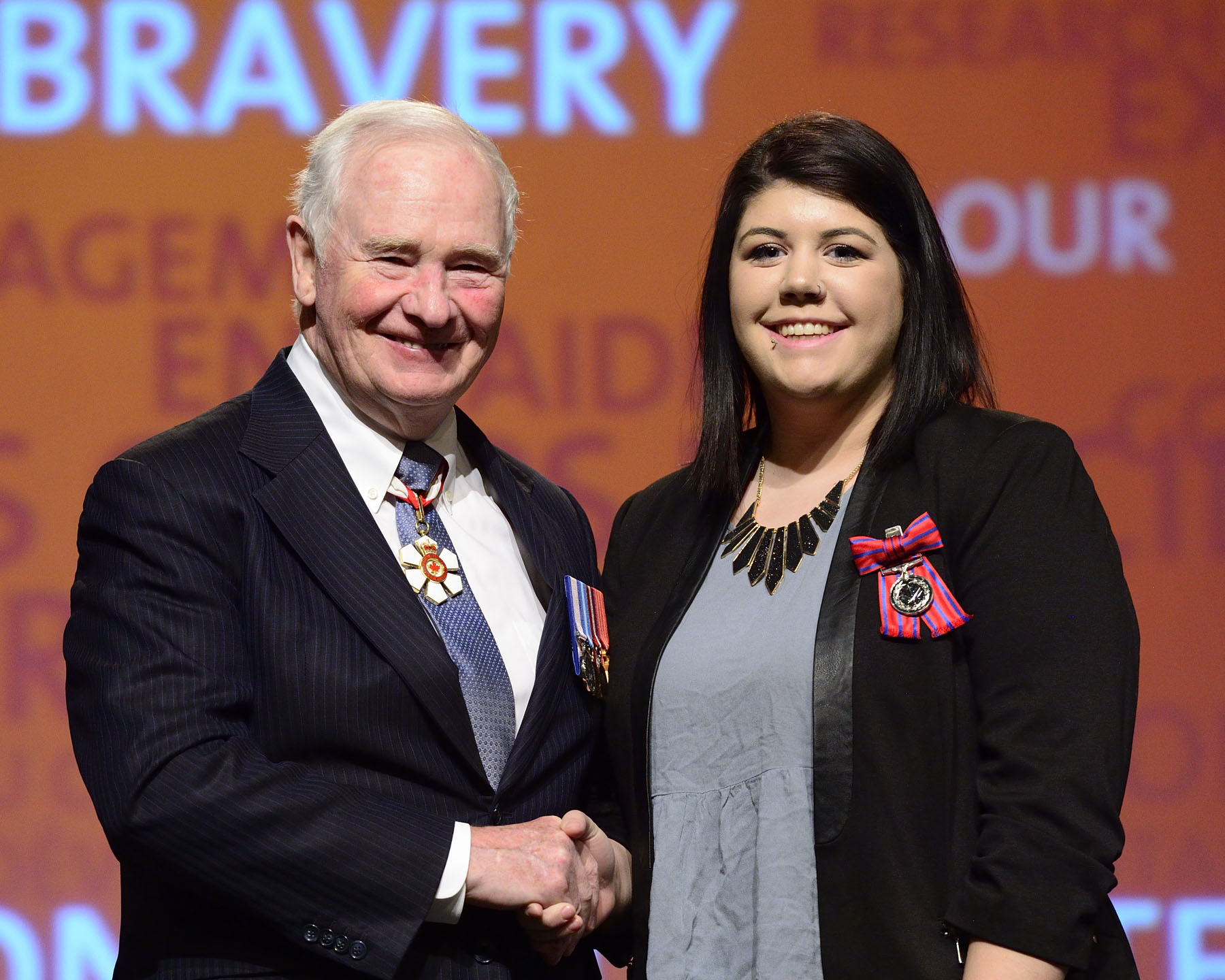 His Excellency presented the Medal of Bravery to Chelsea Little, M.B. On August 11, 2014, then-15-year-old Chelsea Little rescued two people from a possible drowning in Thoburn Lake, near Clarenville, Newfoundland and Labrador. Ms. Little was swimming across the lake with members of her family when she realized that her stepfather was lagging behind and experiencing breathing problems. Chelsea swam back to him and dragged him back to shore just in time to see her uncle in distress before he disappeared beneath the surface. Despite her fatigue, Chelsea dove to reach his side and swam back to shore with him in tow.