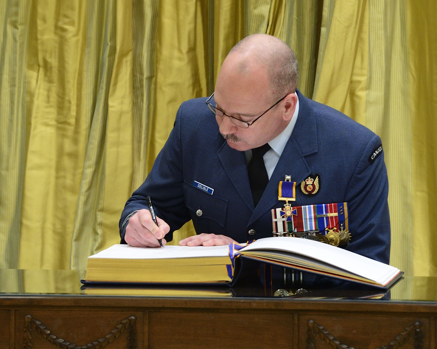Lieutenant-Colonel Joseph Jean Marc Délisle, O.M.M., C.D., signs the register.