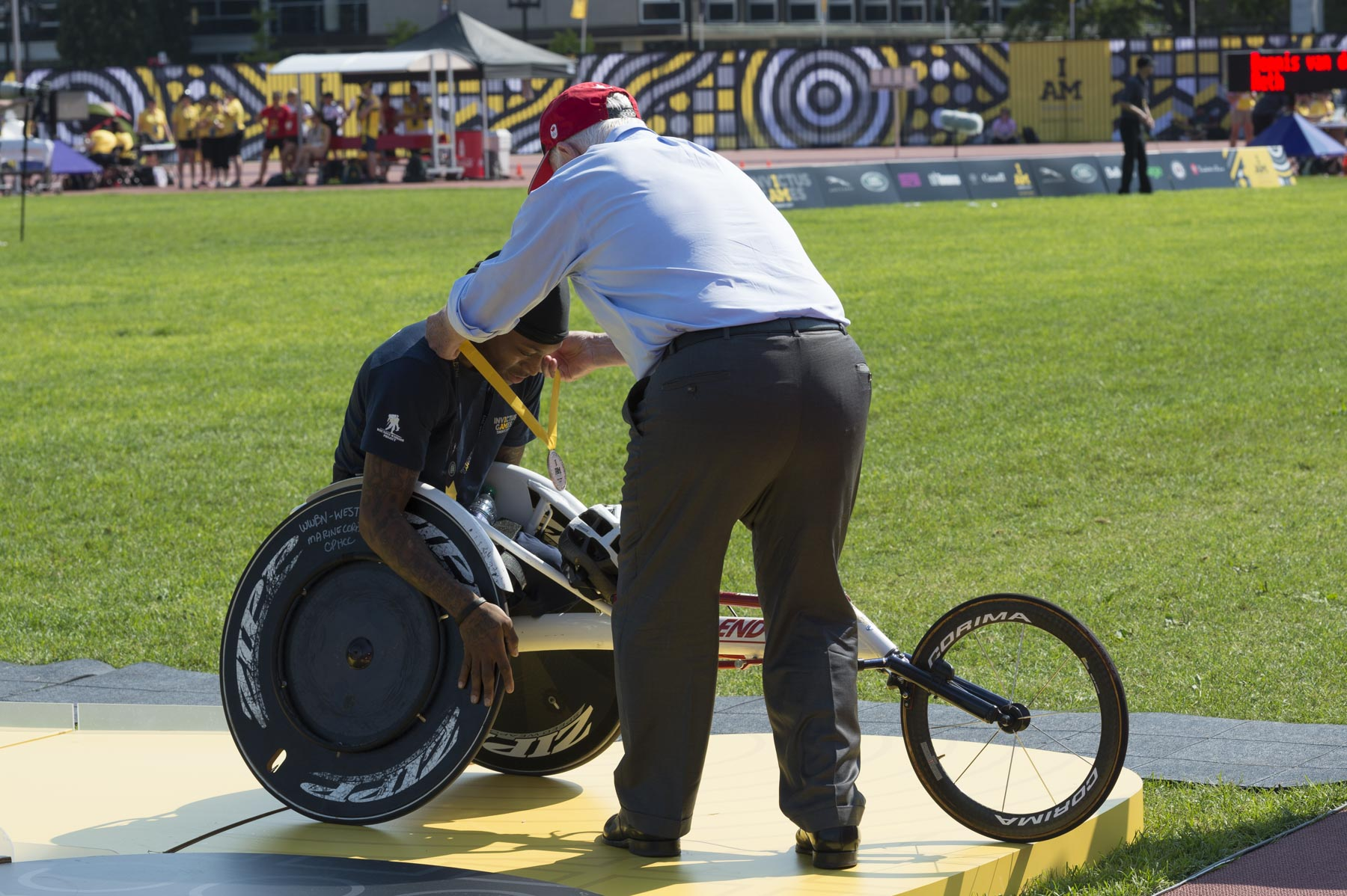 His Excellency then presented medals to the top three competitors in the men's 100-metre wheelchair race.