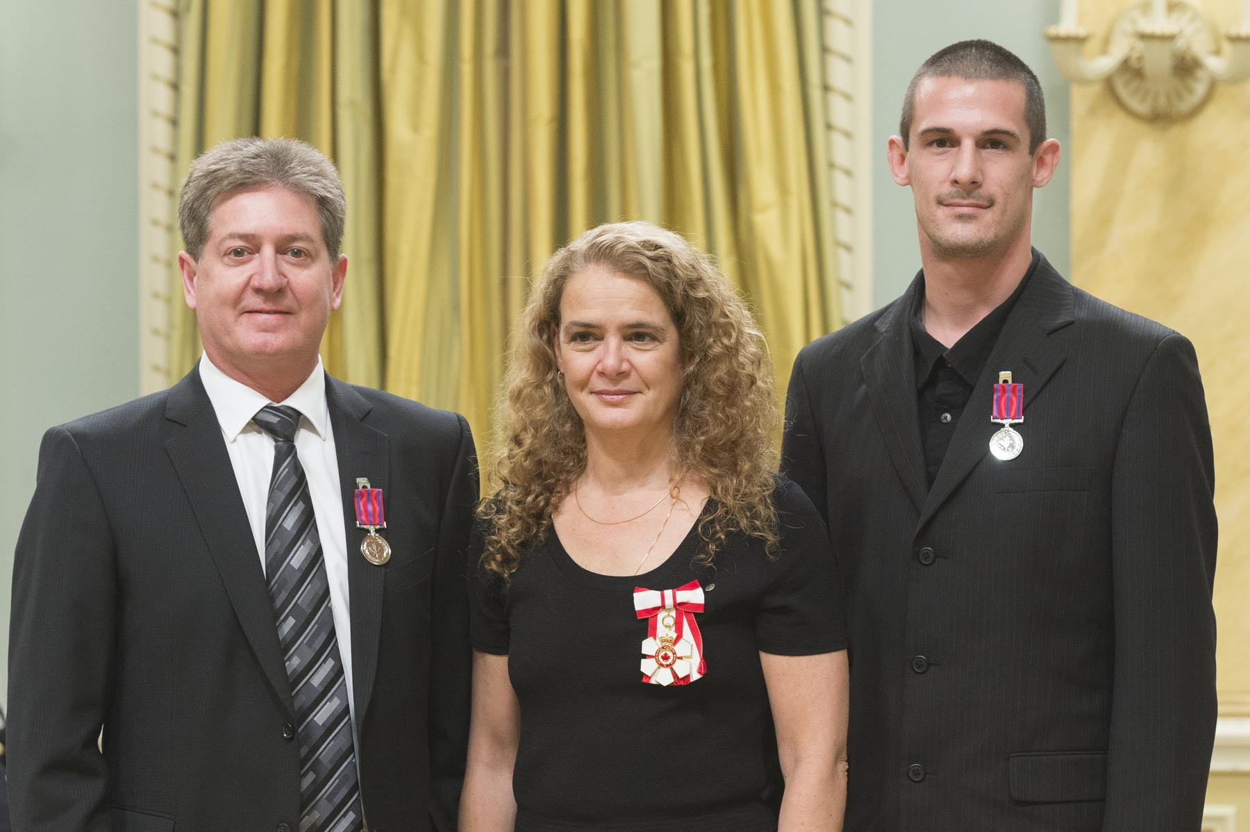 On May 18, 2015, John Gorman and Jim Mascioli intervened in an attack on a young woman, in Timmins, Ontario. The men discovered a car that had crashed into a ditch; inside, they found a woman being stabbed by the driver. Mr. Gorman pulled the victim out of the car, but the assailant followed them out onto the road. After threatening them with his knife, the assailant lunged at the victim, tackled her to the ground and resumed his attack. Mr. Mascioli hauled the man off the woman and restrained him while Mr. Gorman and a bystander cared for the victim until emergency services arrived.