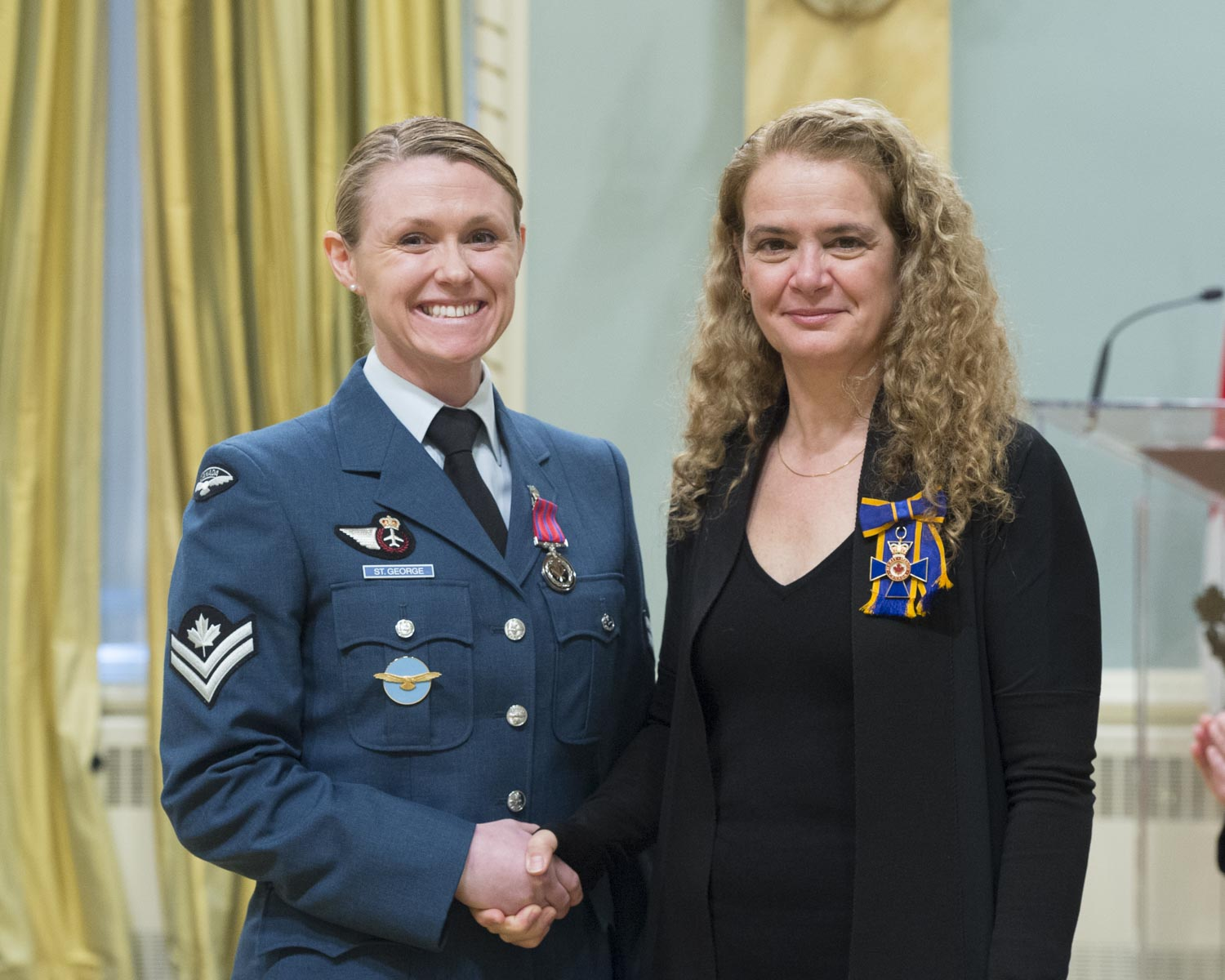 The Governor General presented the Medal of Bravery to Master Corporal Alisha Dawn St.George. On March 11, 2015, Master Corporal Alisha St. George, then-Corporal Fisher, saved a colleague from drowning in the ocean at Torrey Pines State Beach Park, near San Diego, California. The victim had been caught in a rip tide and was struggling to reach the shore. Seeing his predicament, Master Corporal St. George rushed into the water and, after reaching his side, held the distressed man afloat for several minutes. A lifeguard finally reached them and brought the victim to safety, while Master Corporal St. George made it back to shore on her own.