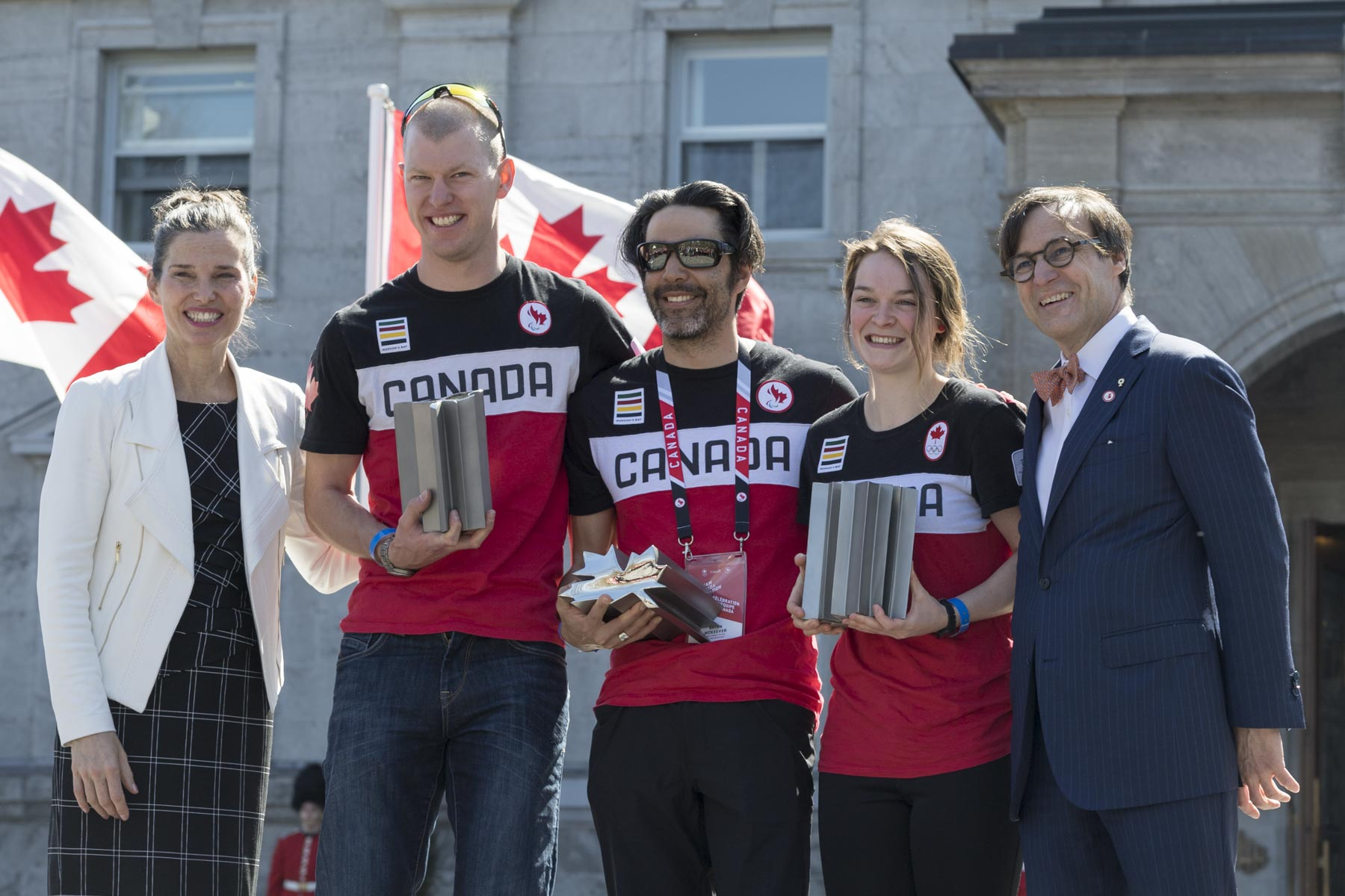 Marc-André Fabien, President of the Canadian Paralympic Committee (far right), and Minister Duncan (far left) presented the James Worrall Flag Bearer Award to (from left to right) Mark Arendz and Brian McKeever, para nordic cross country skiers, as well as to Kim Boutin, short track speed skater.