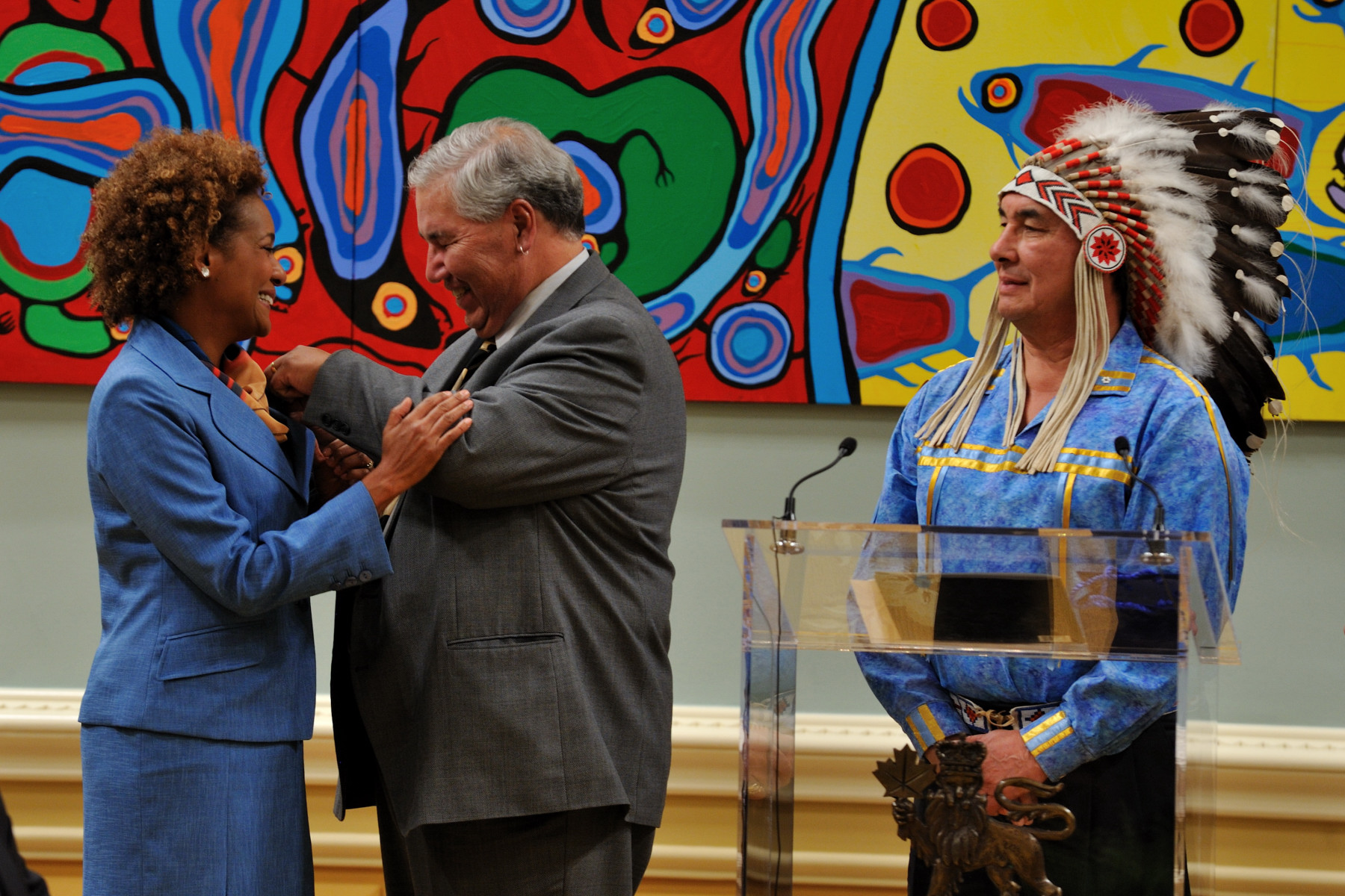 The Honourable Justice Murray Sinclair, Chair of the Commission, offered the official pin of the Commission to Her Excellency while Chief Wilton Littlechild, Commissioner, observed.