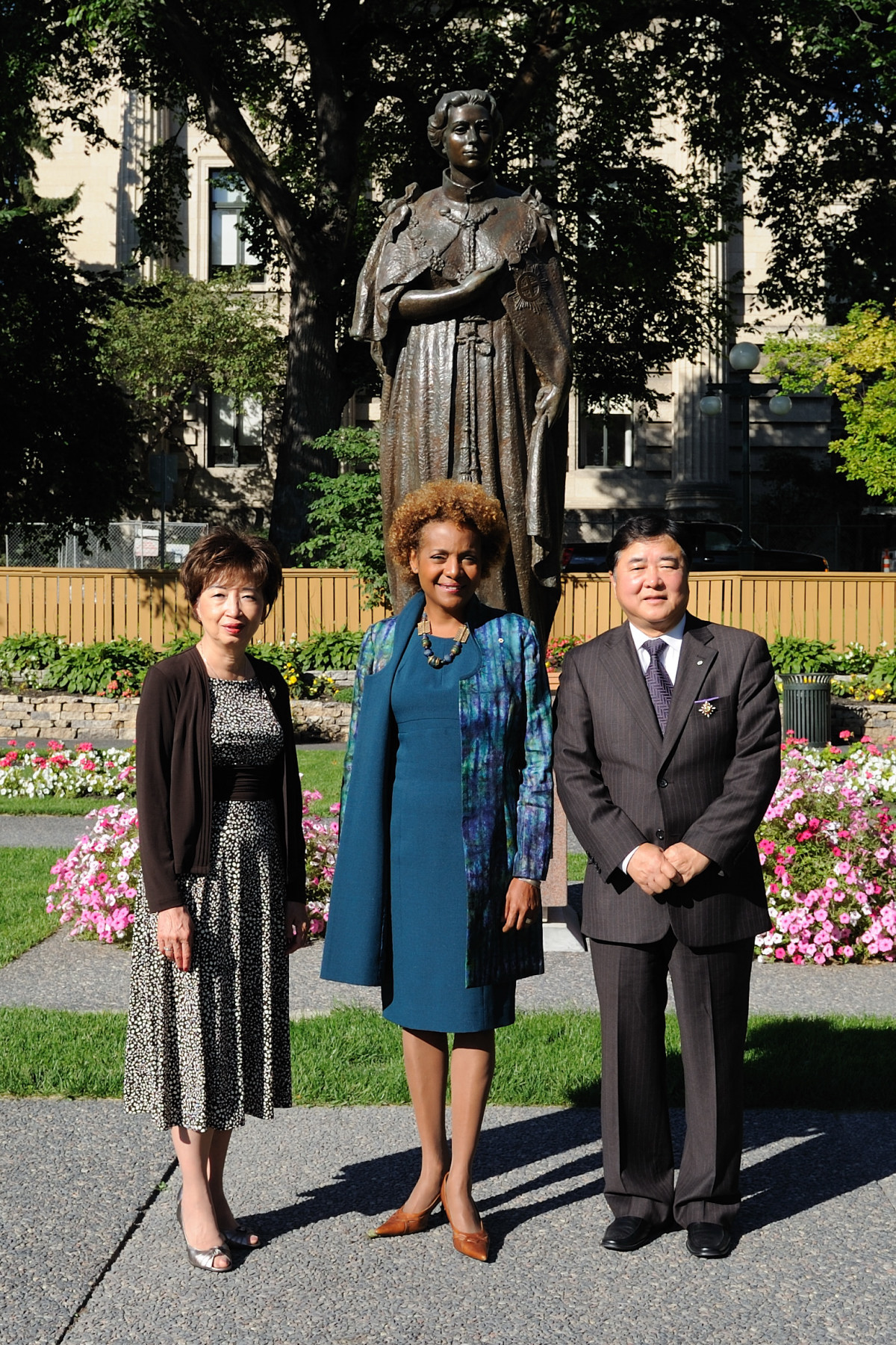 The Governor General with the Lieutenant Governor and his spouse in the gardens in front of a statue of Her Majesty Queen Elizabeth II.