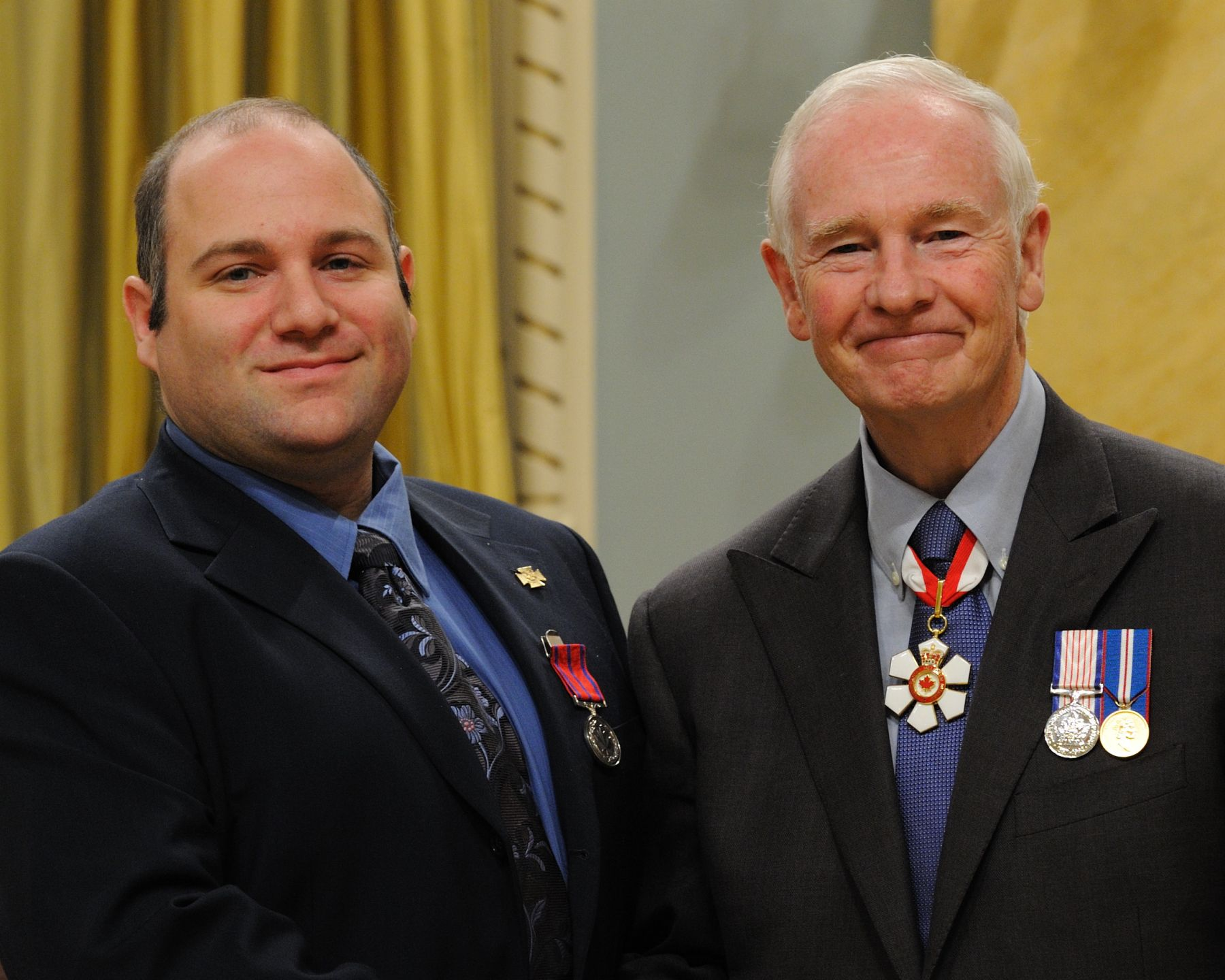 On August 1, 2005, Frédéric Dufresne, M.B. (Trois-Rivières, Quebec) risked his life to prevent a young boy from being hit by an oncoming truck, in Sainte-Monique, Quebec. Mr. Dufresne and his Scout troop were at a roadside rest stop when they noticed a three-year-old boy running towards the roadway, with his father trying to catch him from behind. As Mr. Dufresne joined the chase, the boy ran directly into the path of a transport truck filled with logs. Mr. Dufresne sprinted and tackled the boy, rolling with him until they cleared the road, just as the truck whizzed by.