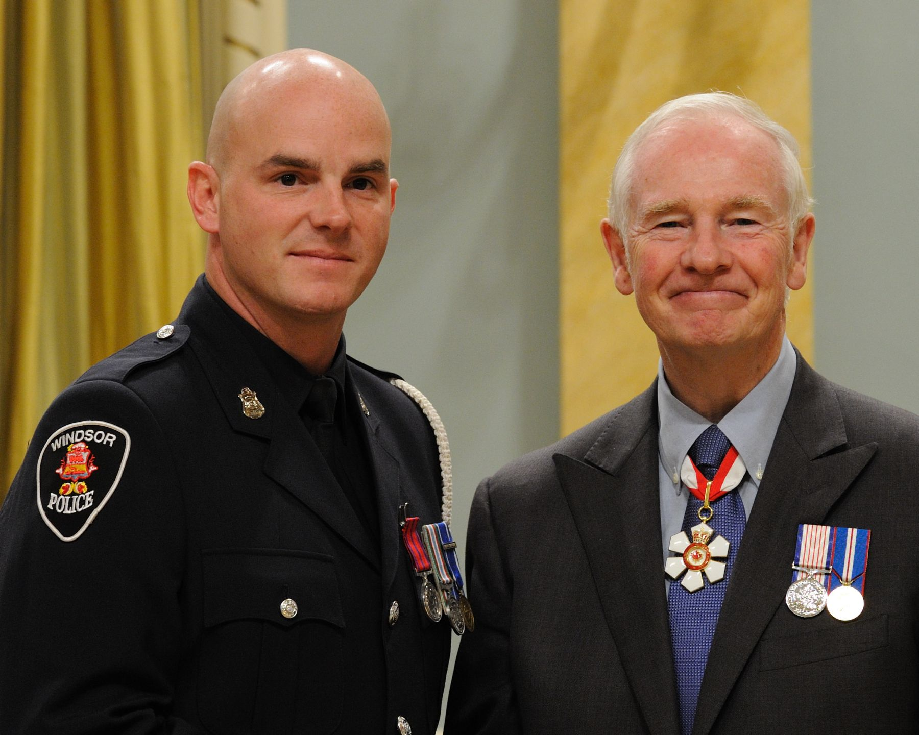On June 17, 2008, constables Michael Gallant, M.B. and Phillip Kolody, M.B. (Windsor, Ontario), of the Windsor Police Service, rescued four people from a burning house, in Windsor, Ontario. On patrol in the area, the constables noticed the fire. Once inside the dwelling, they located and woke the victims. The constables evacuated the family, and returned inside to search for other possible individuals trapped inside. In spite of the flames, the intense heat and the thick black smoke they ensured that no one else was inside, before evacuating nearby homes.