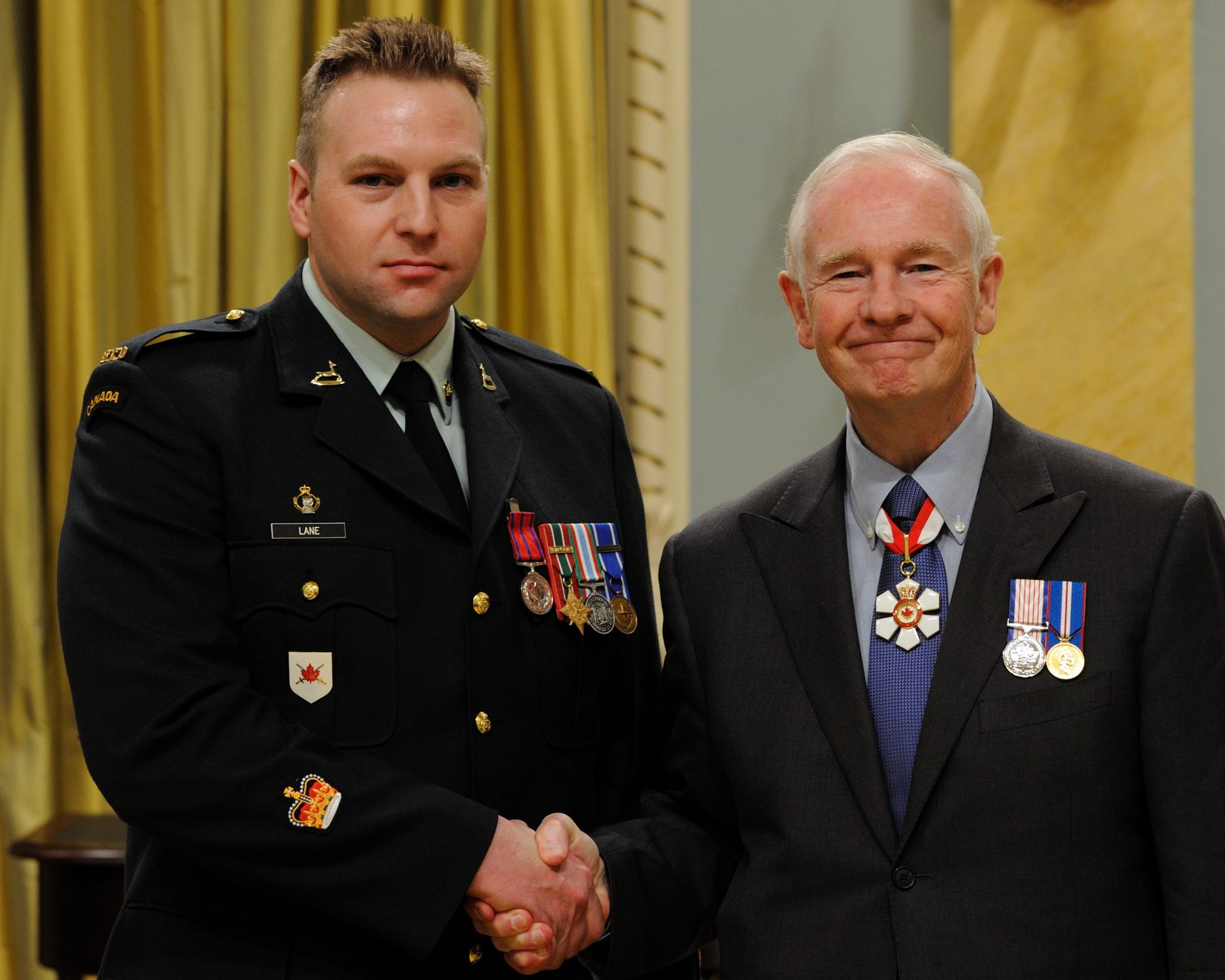 On September 23, 2007, Sergeant Roger Lane, M.B. (Grand Falls-Windsor, Newfoundland and Labrador), then master corporal, apprehended two men who had robbed a grocery store, in Edmonton, Alberta. Sergeant Lane was entering the store when he noticed a man wearing a disguise running towards him and realized that a robbery had just taken place. He caught the suspect, wrestled him to the ground, removed the gun from the suspect's waistband and threw it out of reach. While other shoppers assisted in restraining the robber, Sergeant Lane grabbed a second suspect who was running away. As the man struggled to free himself, he sprayed tear gas in Sergeant Lane's face. Although temporarily blinded, Sergeant Lane managed to subdue him and held onto him until the police arrived minutes later.