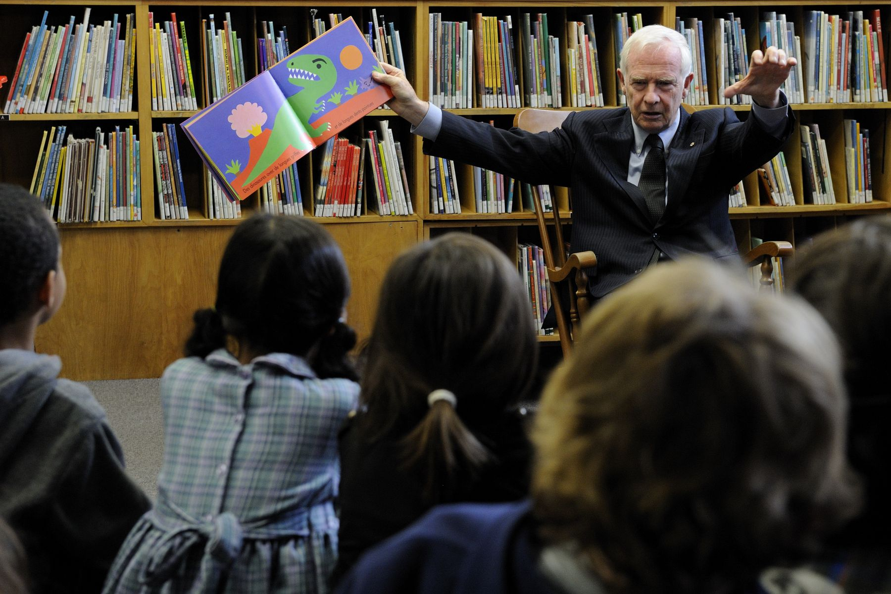 During his visit to the school, the Governor General read a book about dinosaurs to students gathered in the library.