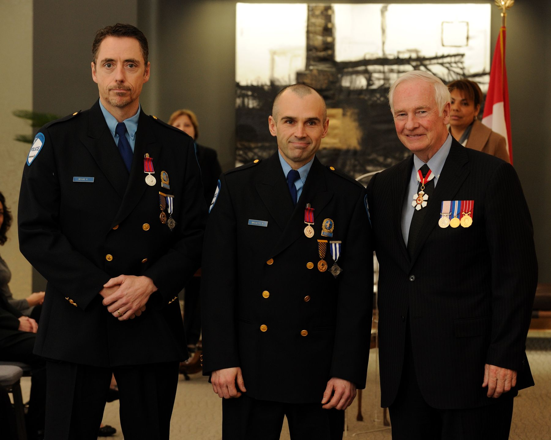 On December 18, 2008, City of Montréal police constables Robert Bérubé, M.B. and Benoit Brissette, M.B., rescued a number of residents from a burning building. The constables had been patrolling the area when they heard an explosion and saw the stone facade of a three-storey building collapse onto the street. The first floor was completely engulfed and the flames were spreading quickly to the apartments above. Without hesitation, the constables ran in as the thick, dark smoke filled the hallway, making it difficult to see and breathe. After evacuating several occupants from the first and second floor apartments, the constables donned gas masks and continued to evacuate all the tenants on the top floor. All residents were eventually brought to safety.