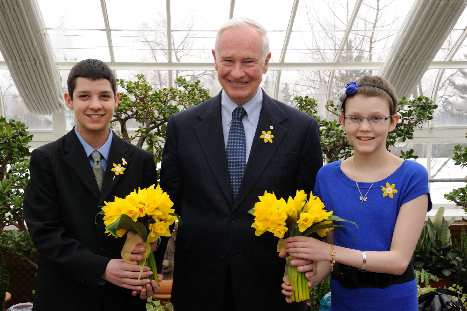 The Governor General posing with Brodie Rafert and Sarah Telford after receiving a bouquet of daffodils to mark the beginning of the Canadian Cancer Society's Daffodil Days campaign for 2011. Funds raised during the campaign will support the most promising cancer research being done in Canada, and will also provide services to people living with cancer and raise awareness about cancer prevention.