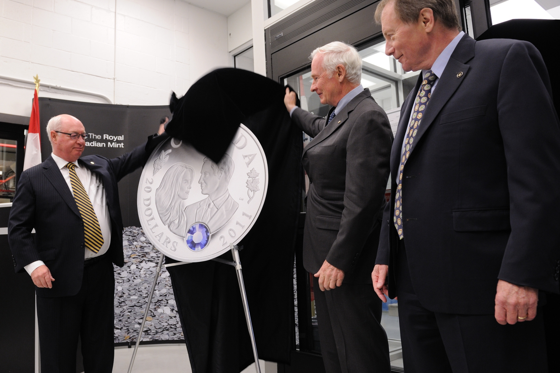 The Governor General and Chairperson of the Board of Directors at the Royal Canadian Mint Mr. James Love (left) unveiled together the first Royal Wedding commemorative coin, a 20 dollar pure silver coin featuring an eye-catching sapphire-coloured crystal enhancement symbolizing the world-renowned 18-carat sapphire engagement ring which Prince William presented to his fiancée in October 2010.