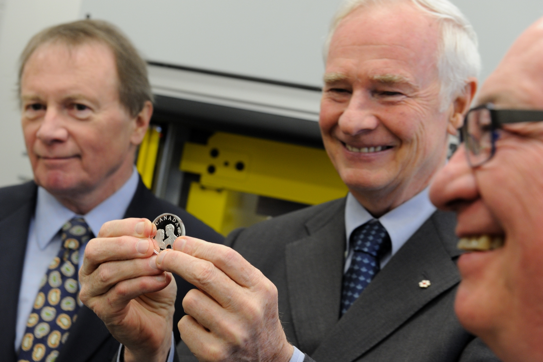 His Excellency proudly showed to media the coin in the presence of Mr. Love (right) and President and CEO of the Royal Canadian Mint Mr. Ian Bennett (left).