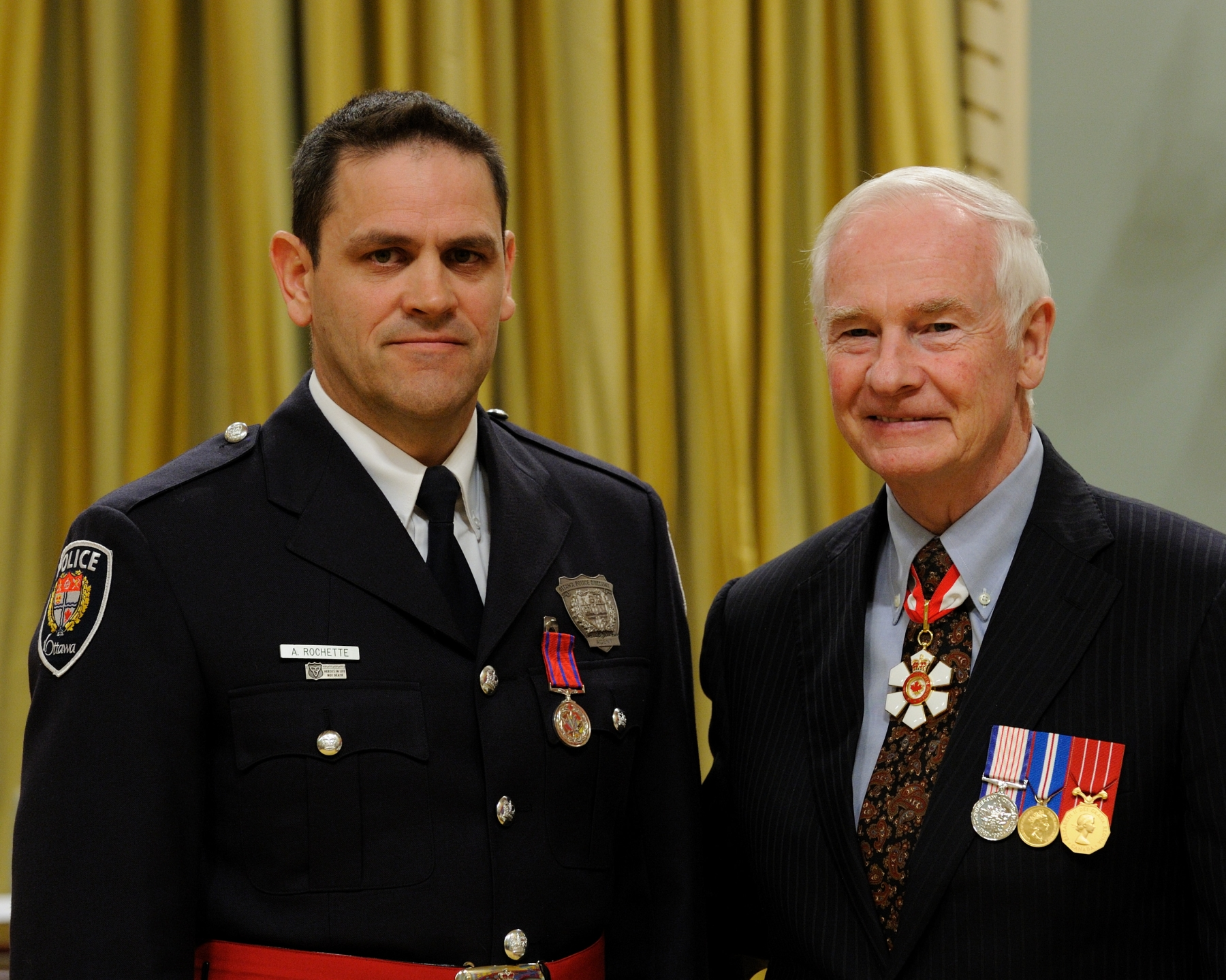 On December 8, 2005, Ottawa police constables Sean Ralph, M.B., and Alain Rochette, M.B. (pictured), risked their lives in an effort to rescue a woman who was being stabbed by a man armed with a hunting knife, in Ottawa, Ontario. When the officers arrived, the attacker grabbed the victim, dragged her inside her basement apartment and locked the door. After numerous attempts to break down the heavy door, the constables succeeded in kicking out a small opening at the bottom of it. Uncertain of what they would encounter on the other side, they crawled into the dark apartment. They spotted the aggressor, who finally responded to the officers' commands and surrendered his weapon. Sadly, the victim did not survive. Constable Ralph received his decoration at a previous ceremony.