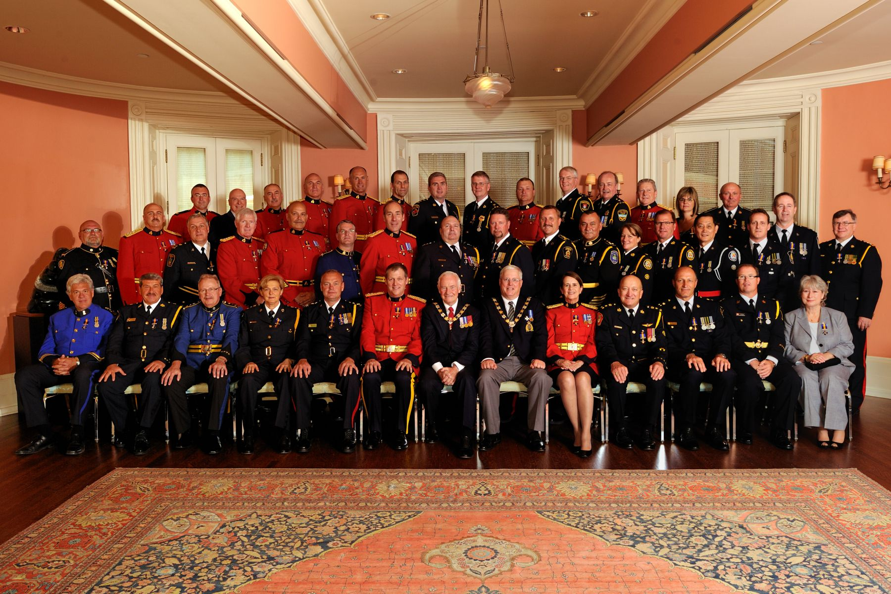 His Excellency and Commissioner Elliott are pictured with the 43 recipients who were invested into the Order of Merit of the Police Forces on June 8, 2011.