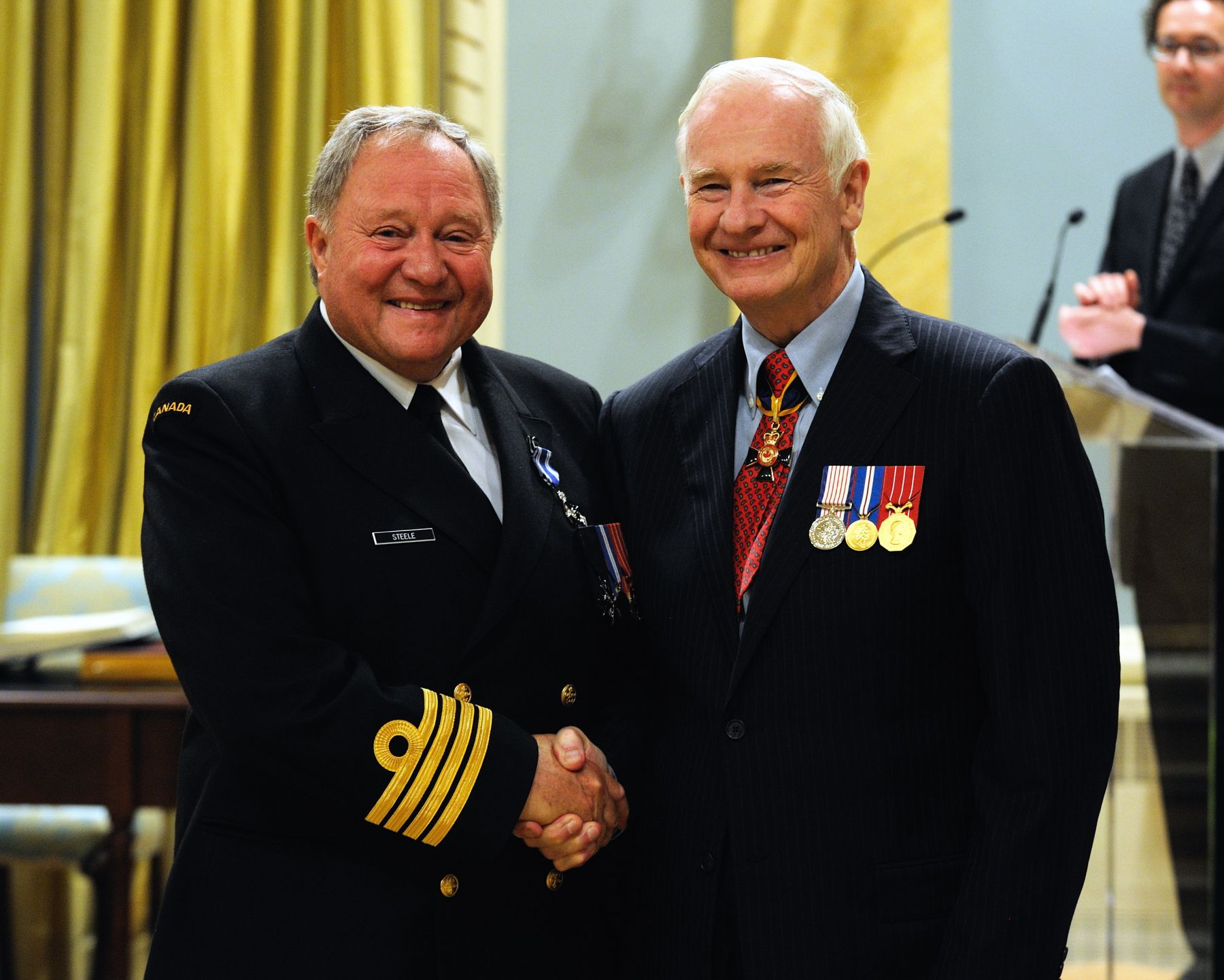 Honorary Captain (N) Cedric Steel, M.S.M., C.D., received the Meritorious Service Medal (Military Division) from His Excellency. In the 13 years since 1997, Honorary Captain (N) Steele's unflagging service to Canadian Forces Base Esquimalt, Maritime Forces Pacific and to the Canadian Forces in general, has inspired and connected the Navy with prominent Canadians and various business groups, as well as the local community. Through Captain (N) Steele's extraordinary energy, vision and tireless efforts, the Esquimalt-based Navy has become linked to the identity of Greater Victoria, as further demonstrated by his commitment to create the Naval Centennial Homecoming statue on the Victoria waterfront.