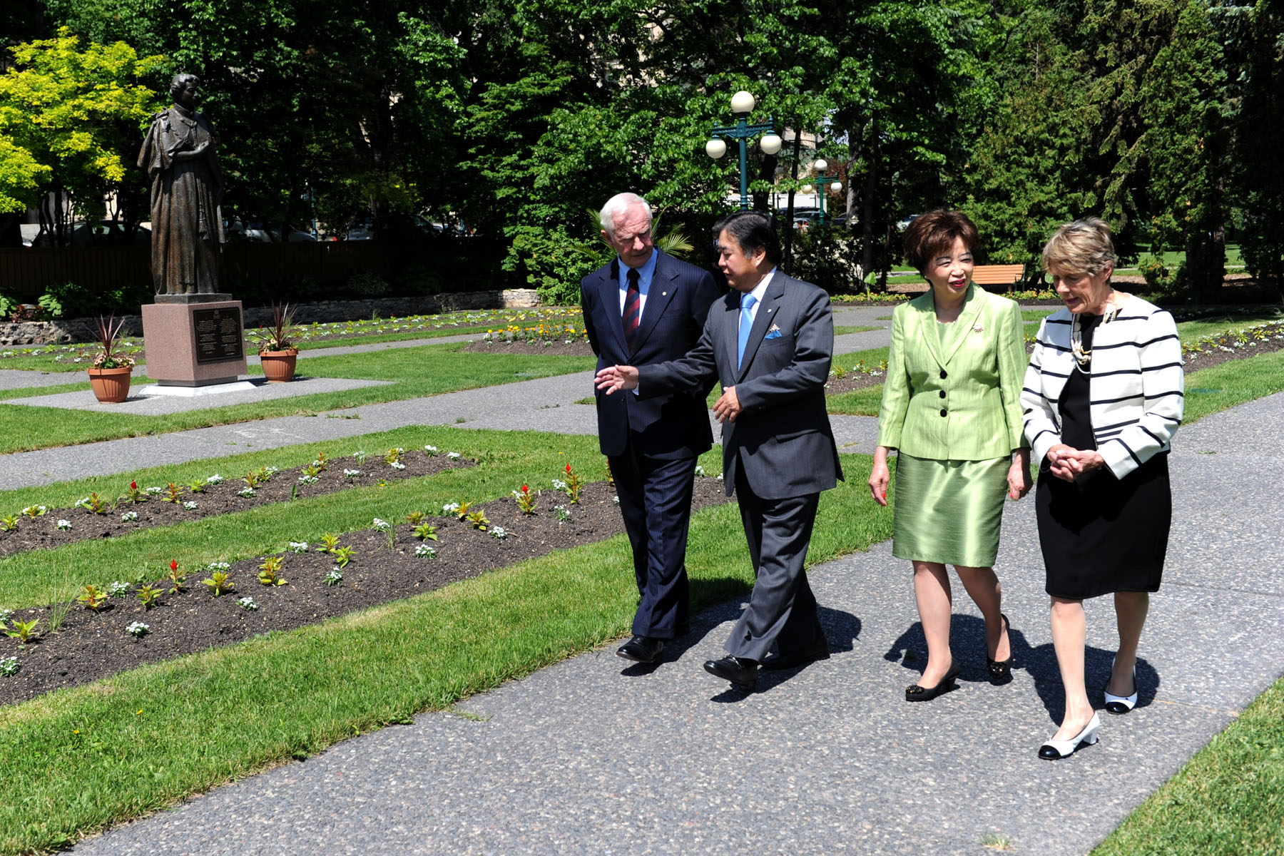 Their Excellencies, accompanied by Their Honours the Honourable Philip Lee, Lieutenant Governor of Manitoba, and his spouse, Mrs. Anita Lee, walking in the gardens at Government House.