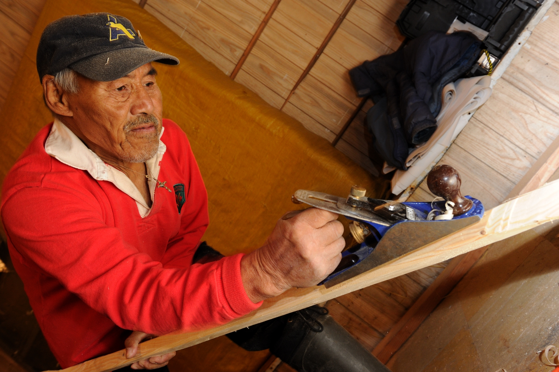 An elder member of the kayak-building workshop provided a demonstration on how to carve a paddle out of wood.