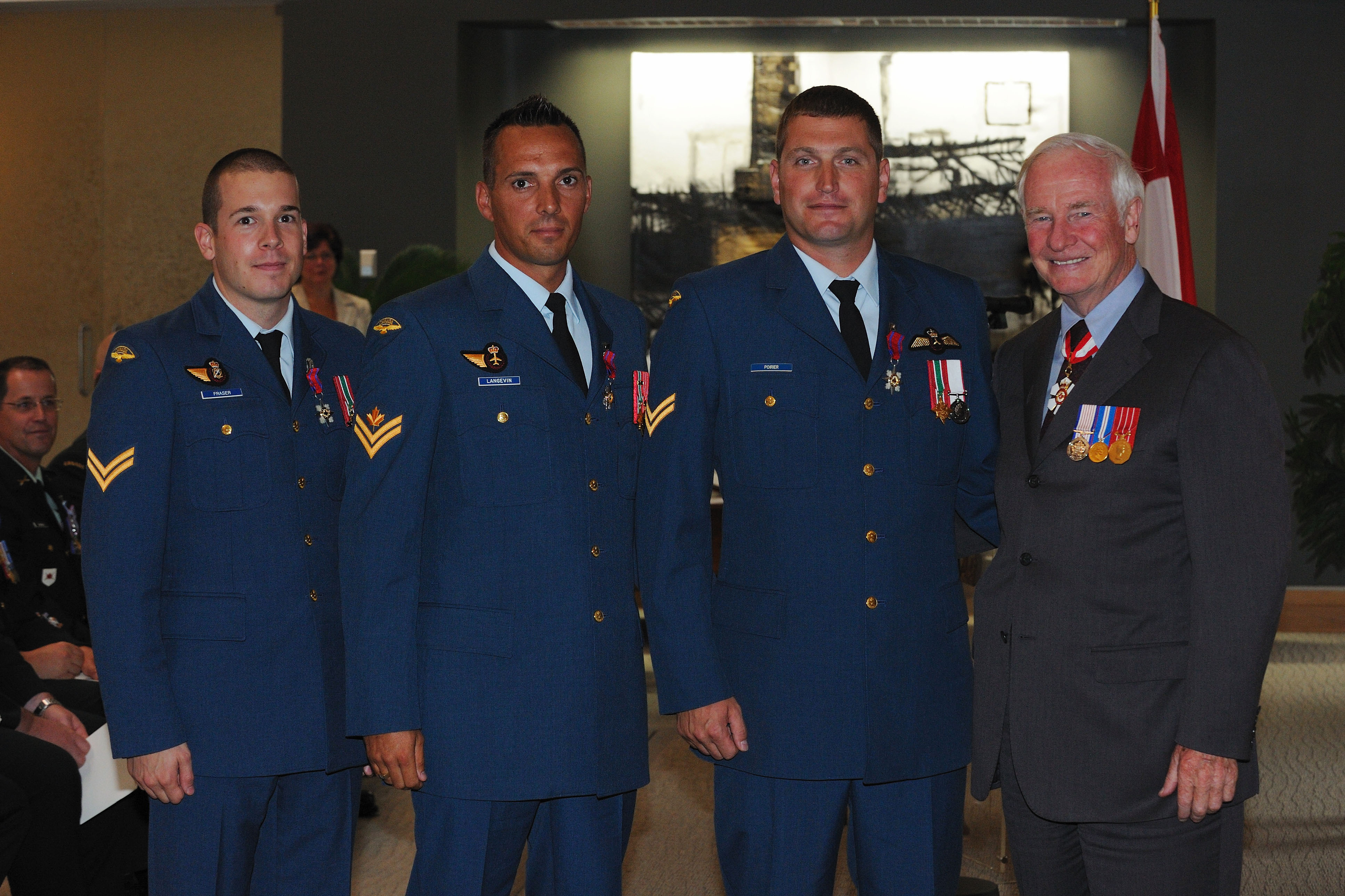Private Adam J. P. Fraser, S.C., Corporal Déri J. G. Langevin, S.C., and Corporal Marc-André Poirier, S.C., received the Star of Courage from His Excellency. On July 19, 2009, corporals Marc-André Poirier and Déri Langevin and Private Adam Fraser demonstrated exceptional courage while helping people who had been injured following the crash of a civilian helicopter at the Kandahar Air Field, in Afghanistan. Alerted to the incident, the three rescuers rushed to the scene outside the security wall of their camp. They crossed a dangerous area engulfed in flames and dodged frequent explosions to reach two victims who were lying in a ditch near the wreckage of their burning helicopter. They moved the wounded to a safe place and provided first aid until medical personnel arrived. The rescuers had to abandon their search for other victims when they realized they were in a minefield. Thanks to the rescuers' efforts, five of the 21 passengers and crew survived.