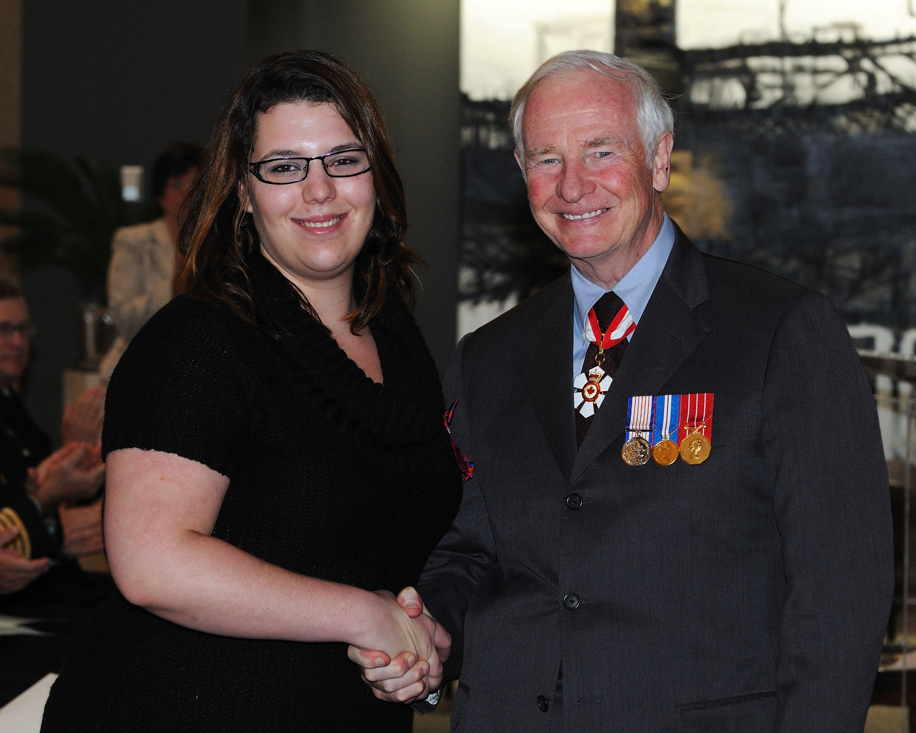Geneviève Otis-Leduc, M.B., received the Medal of Bravery from His Excellency. On June 24, 2009, Ms. Otis-Leduc placed herself at considerable risk to rescue two friends from a possible drowning in the Batiscan River, in Notre-Dame-de-Montauban, Quebec. Ms. Otis-Leduc and her friends had been celebrating Saint-Jean-Baptiste Day when two of them decided to dive into a waterfall. The two friends wound up in turbulent waters, in the middle of the river. One of them suffered an asthma attack, panicked and grabbed onto the other. Ms. Otis-Leduc made her way to them and grabbed the friend who had difficulty breathing. She brought him safely to shore and then swam back to her second friend who, weighed down by his clothing, was in danger of drowning. Although the victim unintentionally pushed her many times below the surface, Ms. Otis-Leduc succeeded in pulling him safely to shore. Her perseverance and brave actions enabled her to save her two friends.