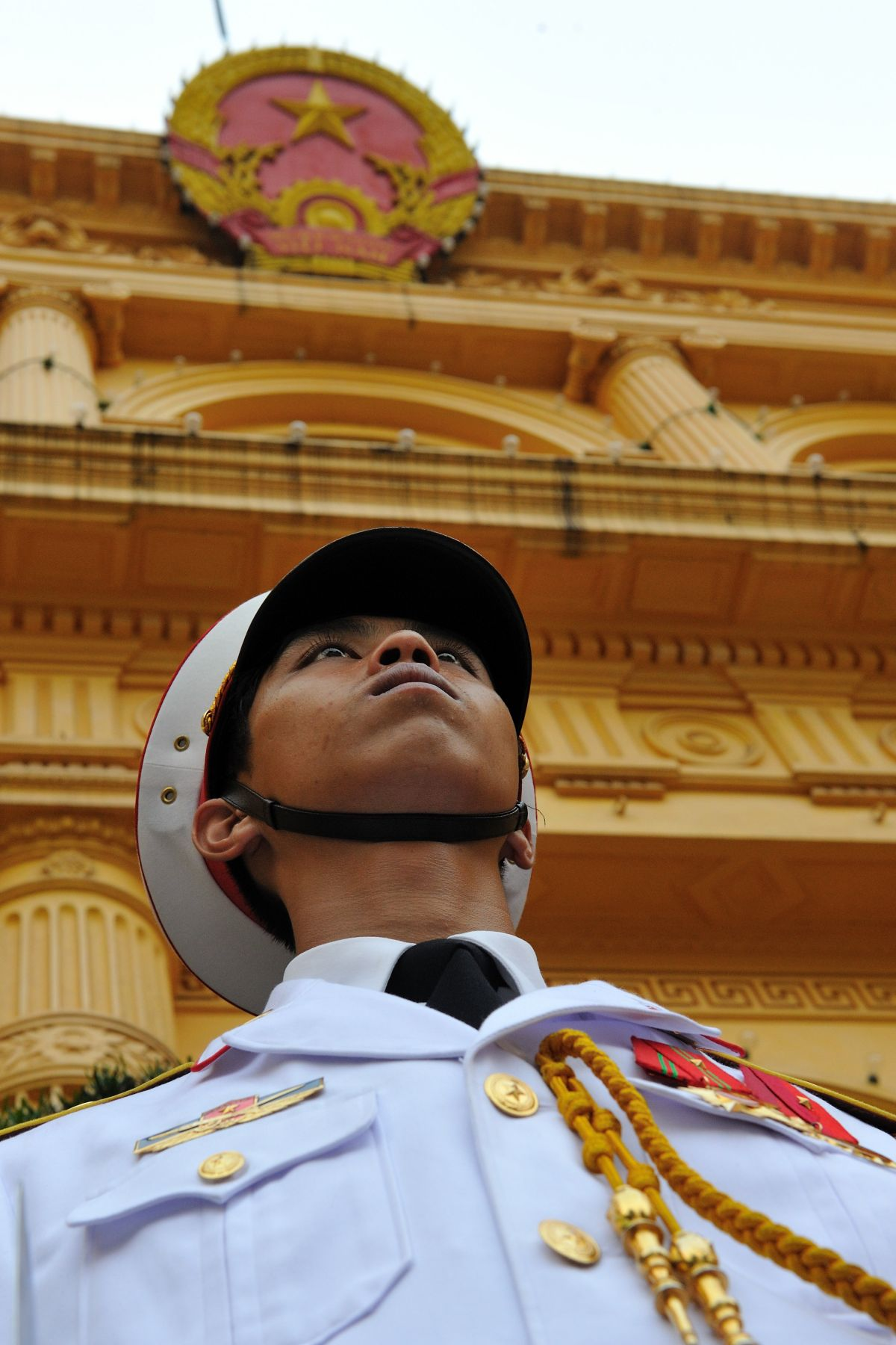 A sentinel stands guard before the Presidential Palace of Vietnam.