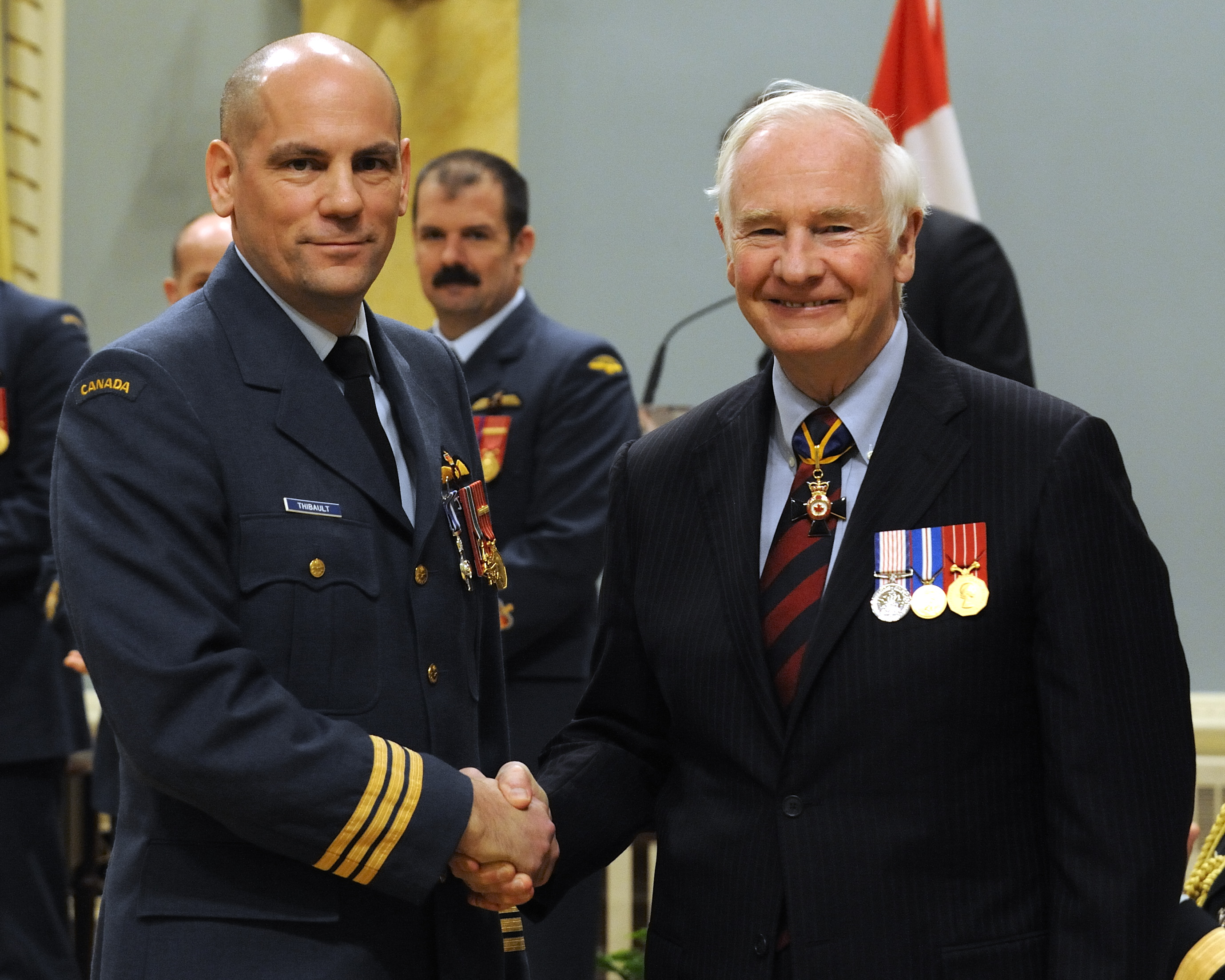 Lieutenant-Colonel Gilbert Clement Thibault, M.S.C., C.D., received the Meritorious Service Cross (Military Division) from His Excellency. On the morning of June 9, 2008, the aircrew of Cormorant Helicopter Rescue 913 successfully evacuated a critically injured sailor from the MV Maersk Dunedin, near Halifax. Aircraft Commander Lieutenant-Colonel Thibault made critical command decisions as he piloted the aircraft under exceptionally demanding circumstances. He was assisted by First Officer Captain Mercer, who helped fly the aircraft for nearly 10 hours, twice landing on Sable Island for fuel as the aircraft's endurance was pushed to its limits.  In conditions where visibility was so poor that they could not even see the vessel in distress, flight engineer Sergeant Pawulski was instrumental in providing advice to help guide the aircraft into position over the deck in order to facilitate the hoist operation.  Search and rescue technicians Warrant Officer Mitchell and Sergeant Kelland were then lowered onto the heaving deck, where they rendered life-saving medical aid to the injured sailor and coordinated his removal to the rescue helicopter.  The team's conduct, dedication and professionalism in the planning and execution of this daring rescue brought great credit to the Canadian Forces.