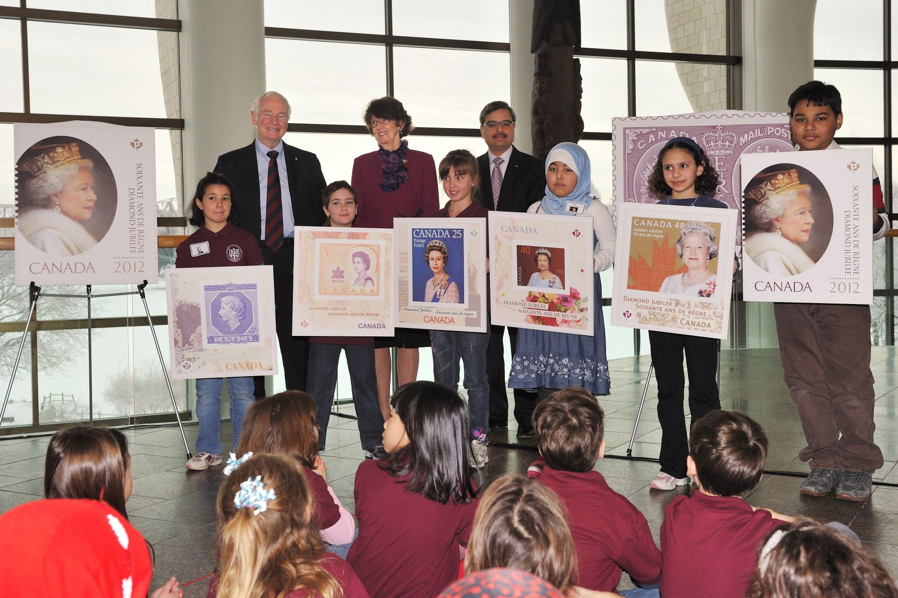 The Right Honourable David Johnston, Governor General of Canada, along with the Honourable Marjory LeBreton, Leader of the Government in the Senate, Mr. Deepak Chopra, President and Chief Executive Officer of Canada Post, and third grade students from two Ottawa-Gatineau area schools, unveiled commemorative stamps in celebration of Her Majesty Queen Elizabeth II's Diamond Jubilee.