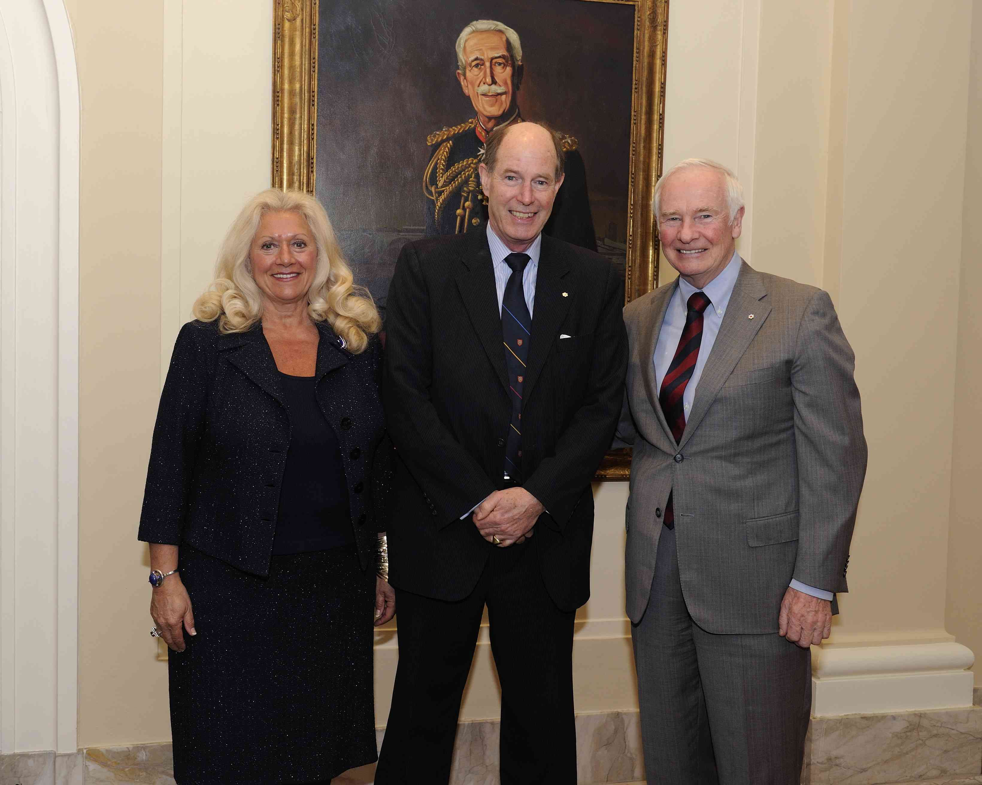 Dr. David Dodge is surrounded by Ms. Maria David-Evans and the Governor General. The Vanier Medal was created in 1962 in honour of Canada's second Canadian-born governor general, the Right Honourable Georges P. Vanier (seen in the portrait on the wall).