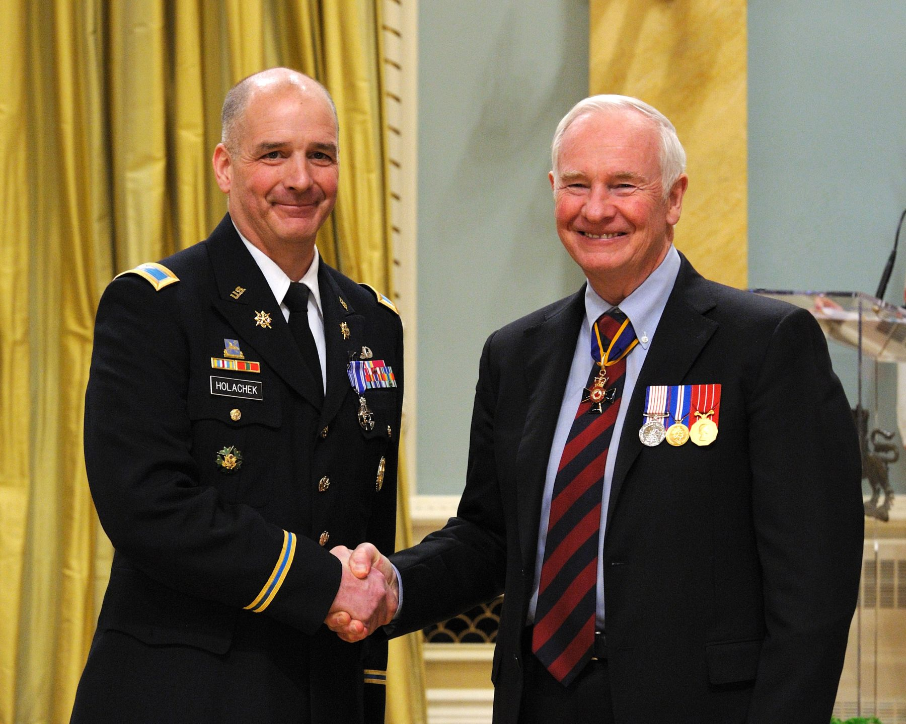 Colonel Jeffrey Holachek, M.S.M. (United States Army), received the Meritorious Service Medal (Military Division) from His Excellency. Colonel Holachek, of the United States Army, consistently demonstrated strong leadership and outstanding professionalism. He developed and employed innovative concepts, effectively led his staff through complex operational planning, and delivered effective plans for implementation. Colonel Holachek's dedication and unwavering commitment greatly enhanced the operational effectiveness of expeditionary operations and brought great credit to Canada.