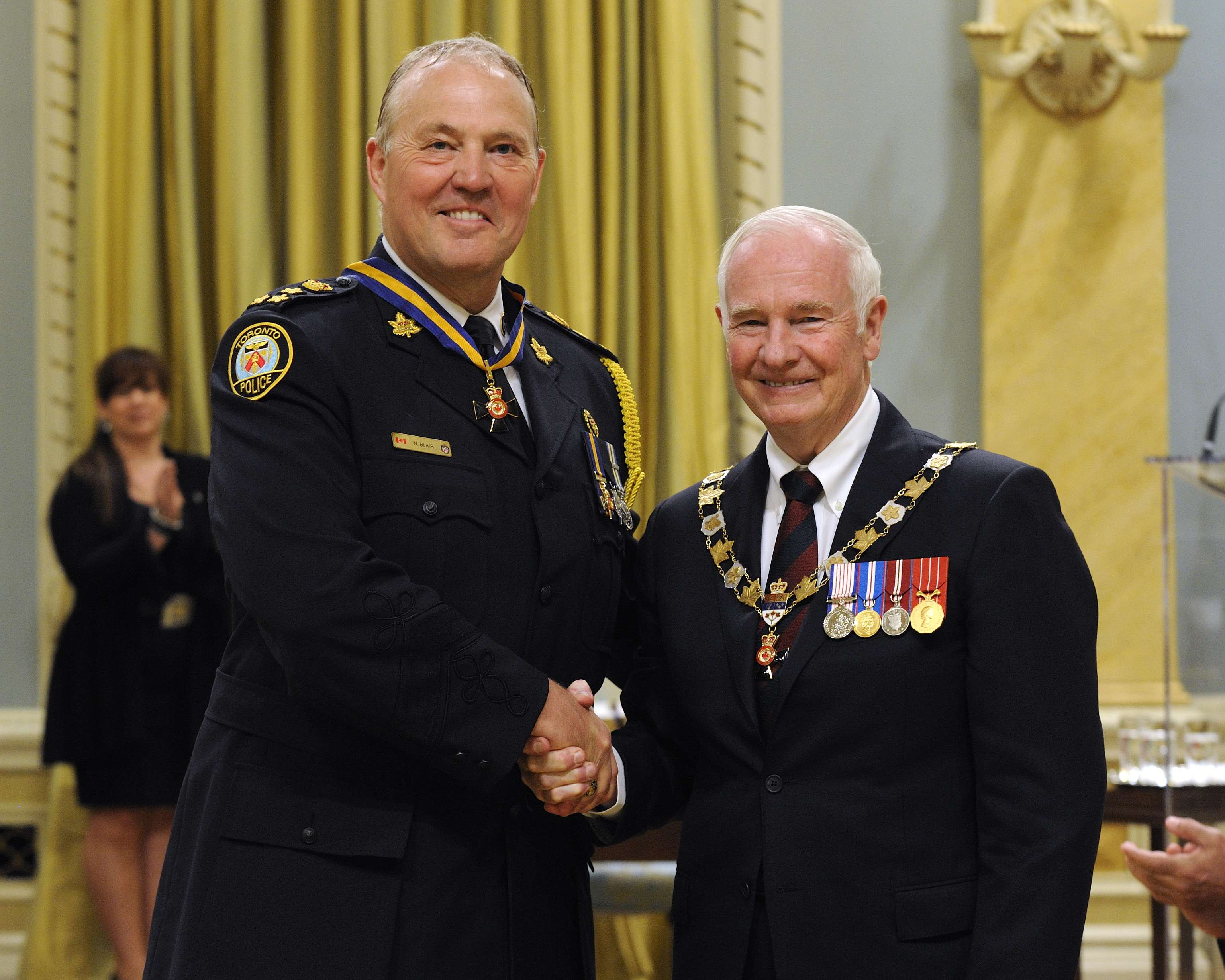 His Excellency presented the Order of Merit of the Police Forces at the Commander level (C.O.M.) to Chief William Sterling Blair, C.O.M., of the Toronto Police Service, Ontario. This is a promotion within the Order.