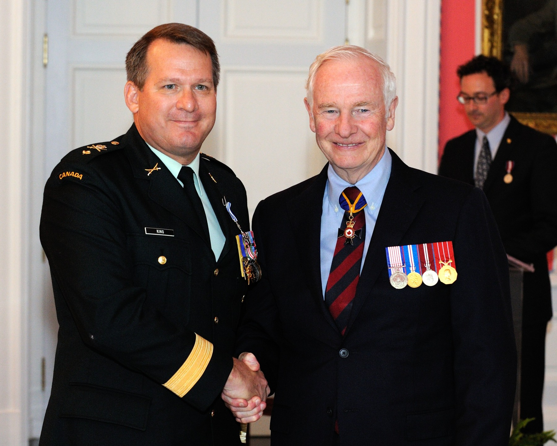 Brigadier-General Craig Randall King, O.M.M., M.S.C., C.D., M.B.E., received the Meritorious Service Cross (Military Division) from His Excellency. While deployed within Regional Command (South) in Afghanistan from December 2009 to September 2010, Brigadier-General King played a critical role during a defining moment in the campaign. As the driving force behind the expansion of Afghan National Security Forces, particularly the Afghan National Police, he worked with Afghan and coalition stakeholders to institute a complete review of personnel and equipment that provided an accurate assessment of the current situation and facilitated decision making. Brigadier-General King's leadership and work ethic contributed to the improvement of the security situation in southern Afghanistan and brought great credit to Canada and the Canadian Forces.