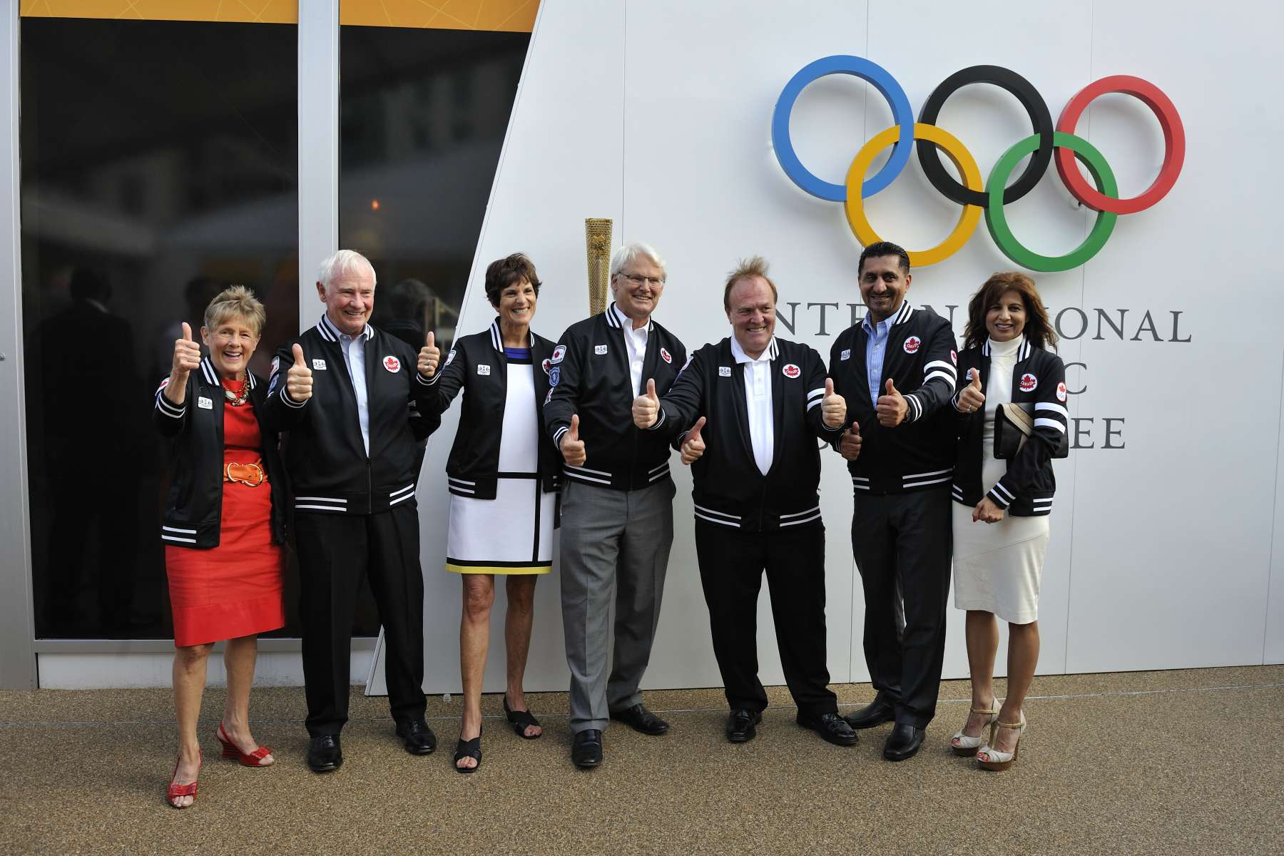 During their visit to the Olympic Village, Their Excellencies were accompanied by (from right to left) the Honourable Bal Gosal, Minister of State (Sport), and Mrs. Pawanjit Gosal, Mr. Marcel Aubut, President of the COC, Gordon Campbell, High Commissioner for Canada, and Mrs. Nancy Campbell. They were presented with a Team Canada Athletes' Podium Replica Jackets by Mr. Aubut.
