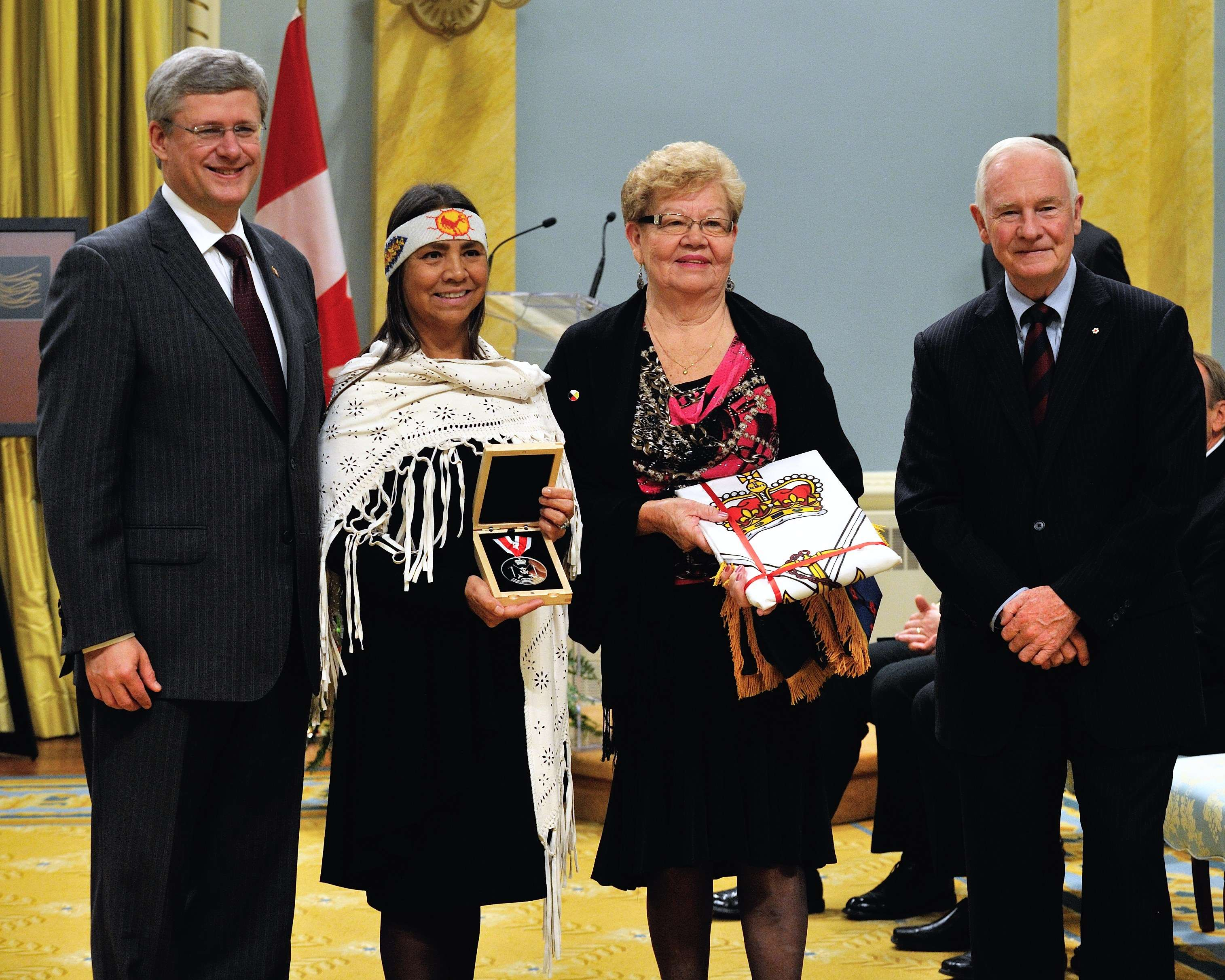 On the occasion of the War of 1812 National Recognition Ceremony, His Excellency, accompanied by the Right Honourable Stephen Harper, Prime Minister of Canada, presented First Nations and Métis communities with a Commemorative War of 1812 medal and banner. In the photo, the Prime Minister and the Governor General are with Chief Sharon Stinson Henry and Myrna Watson, representatives of Chippewas of Rama First Nation.
